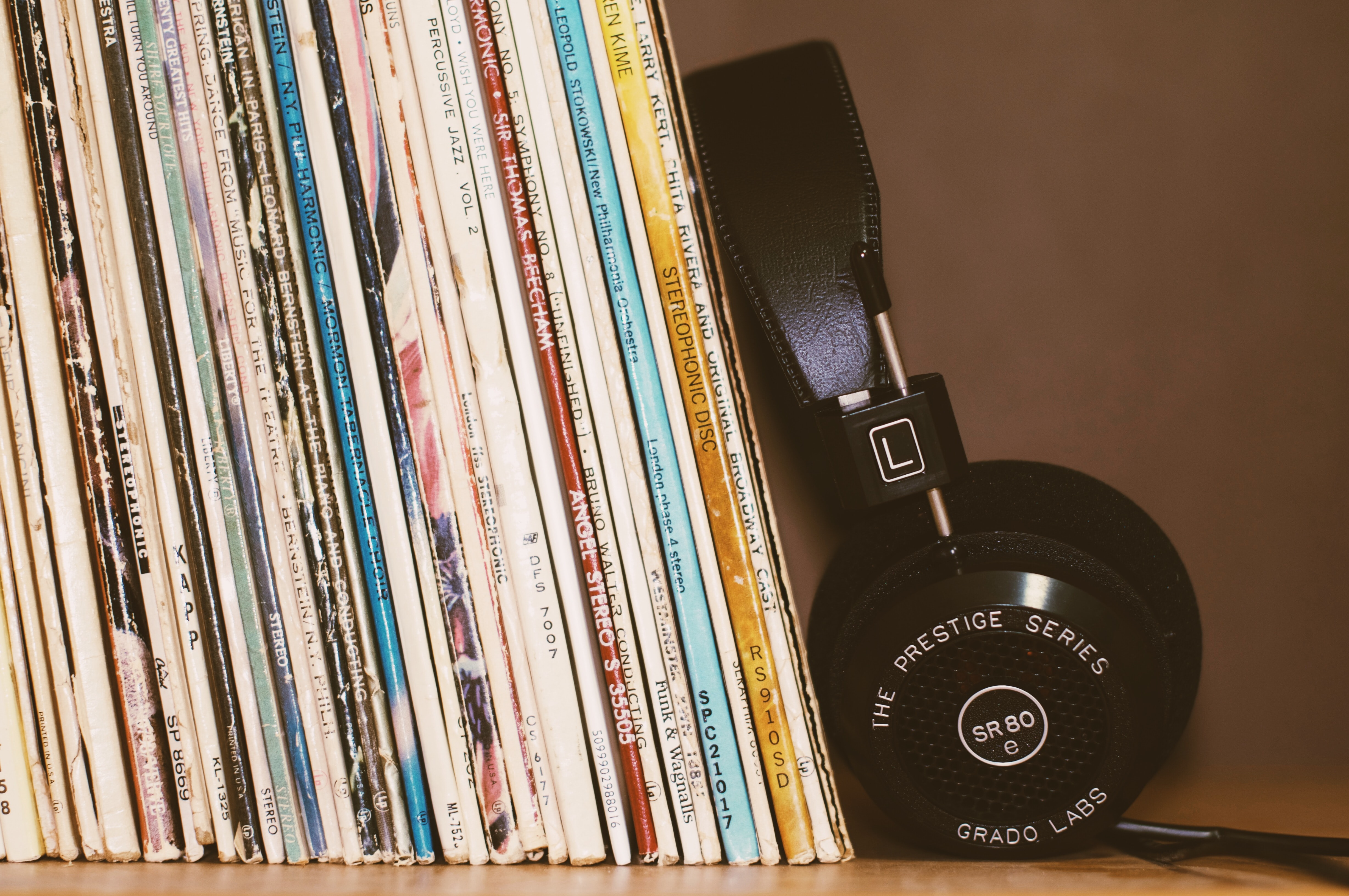 Black headphones leaning against a collection of vinyl records on a shelf