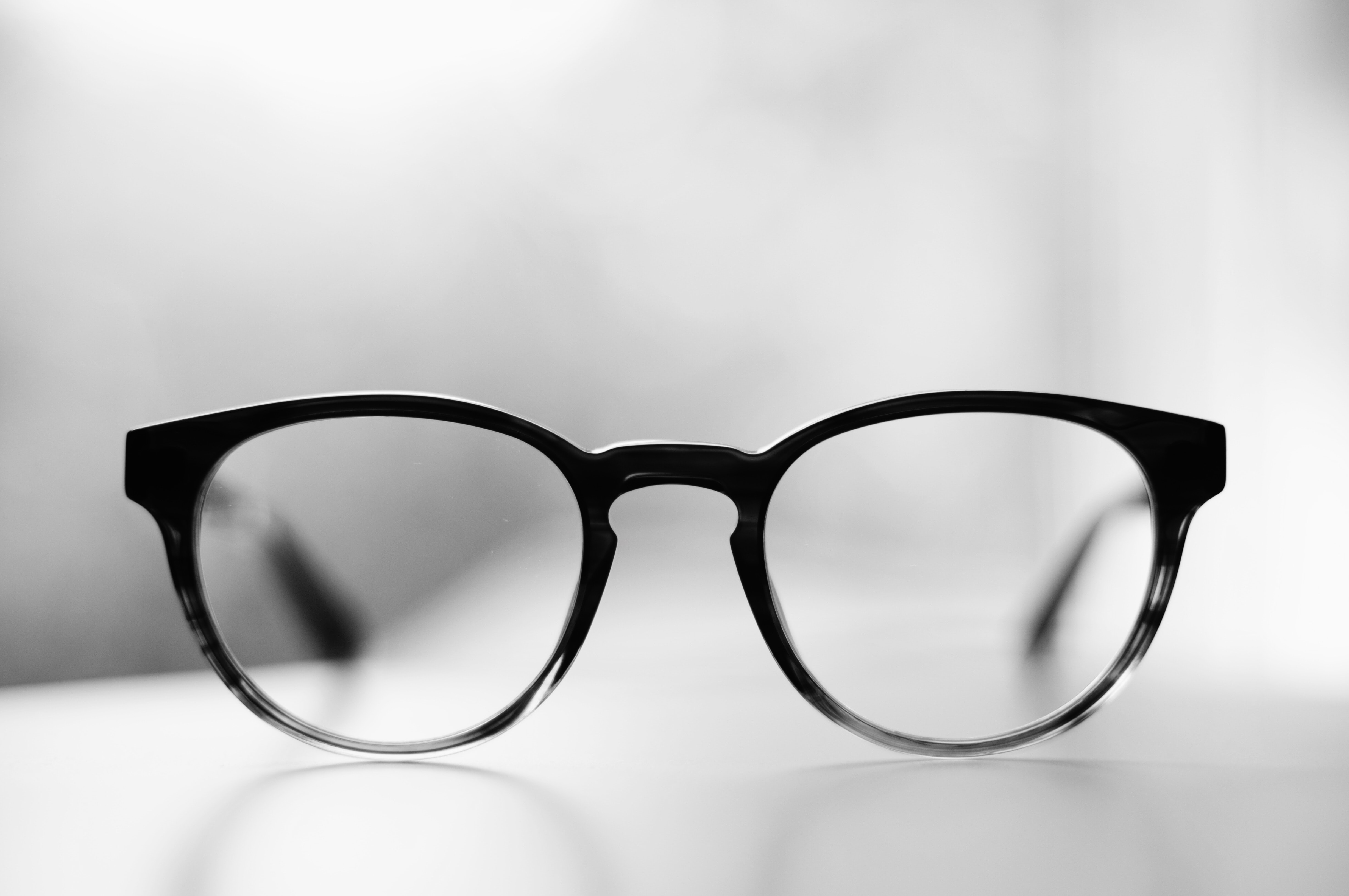 A pair of glasses in black frames on a white surface