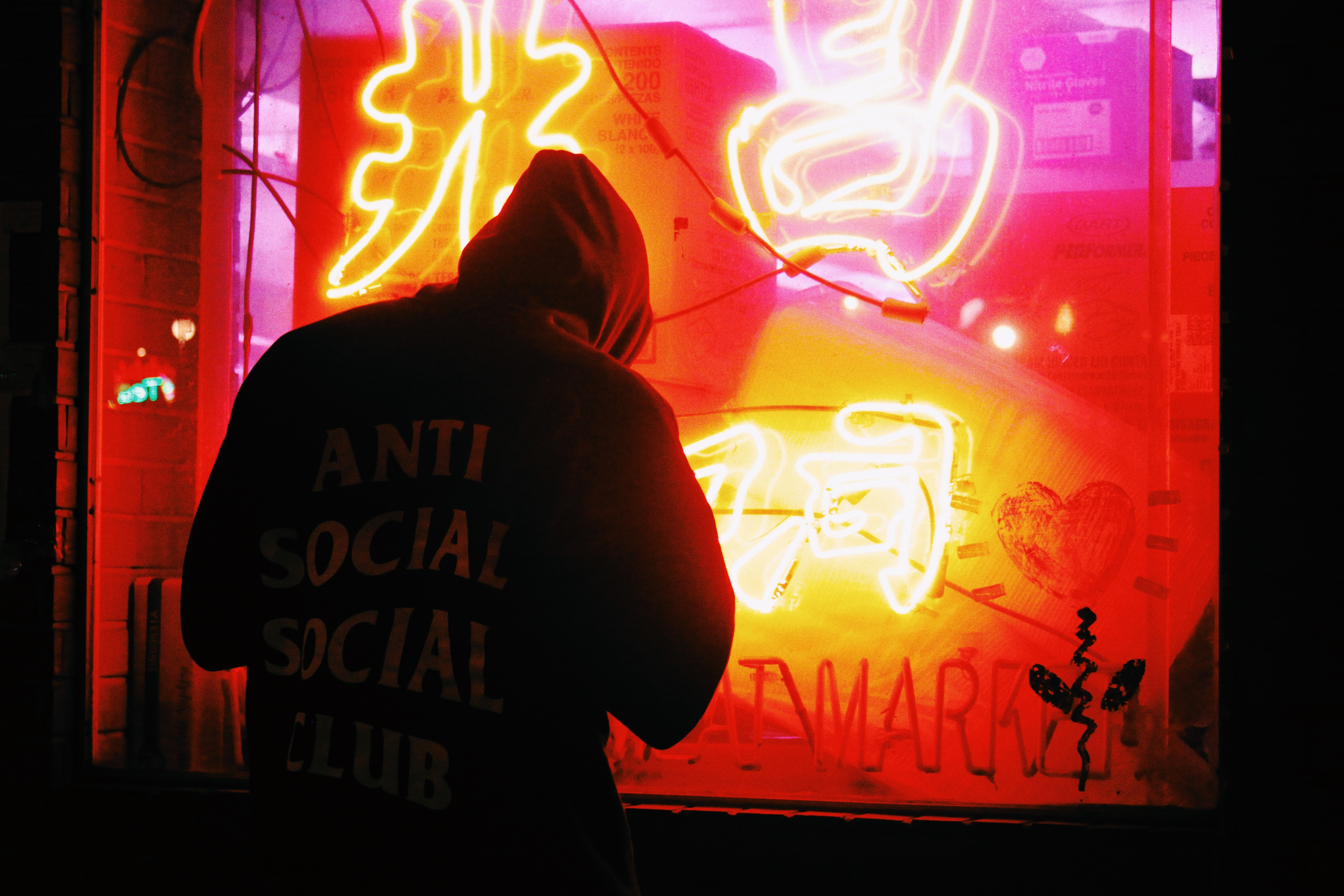 Man in hoody with anti social slogan standing outside red neon display in store window