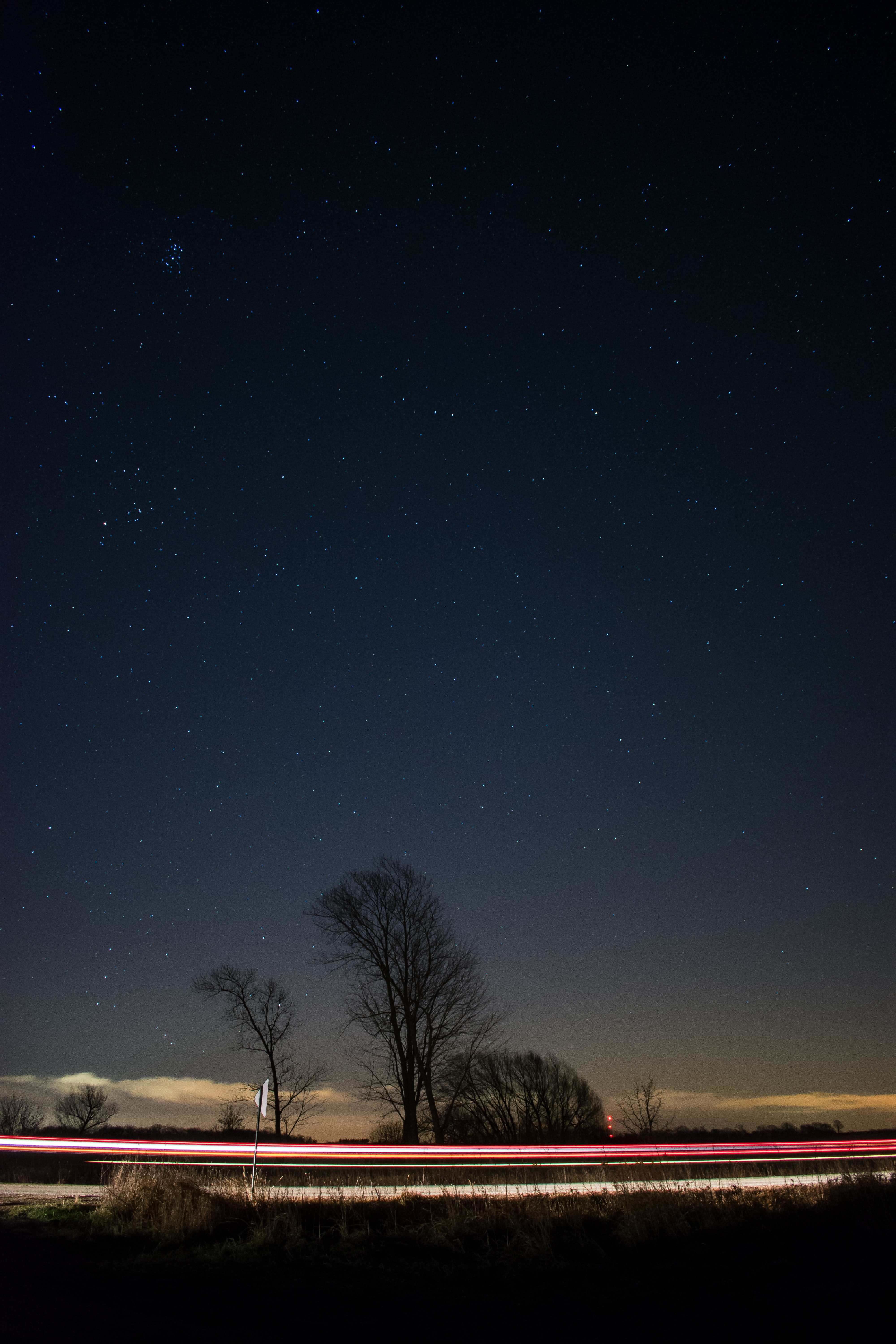 A light rail image with a dark night sky and tree silhouettes in the horizon