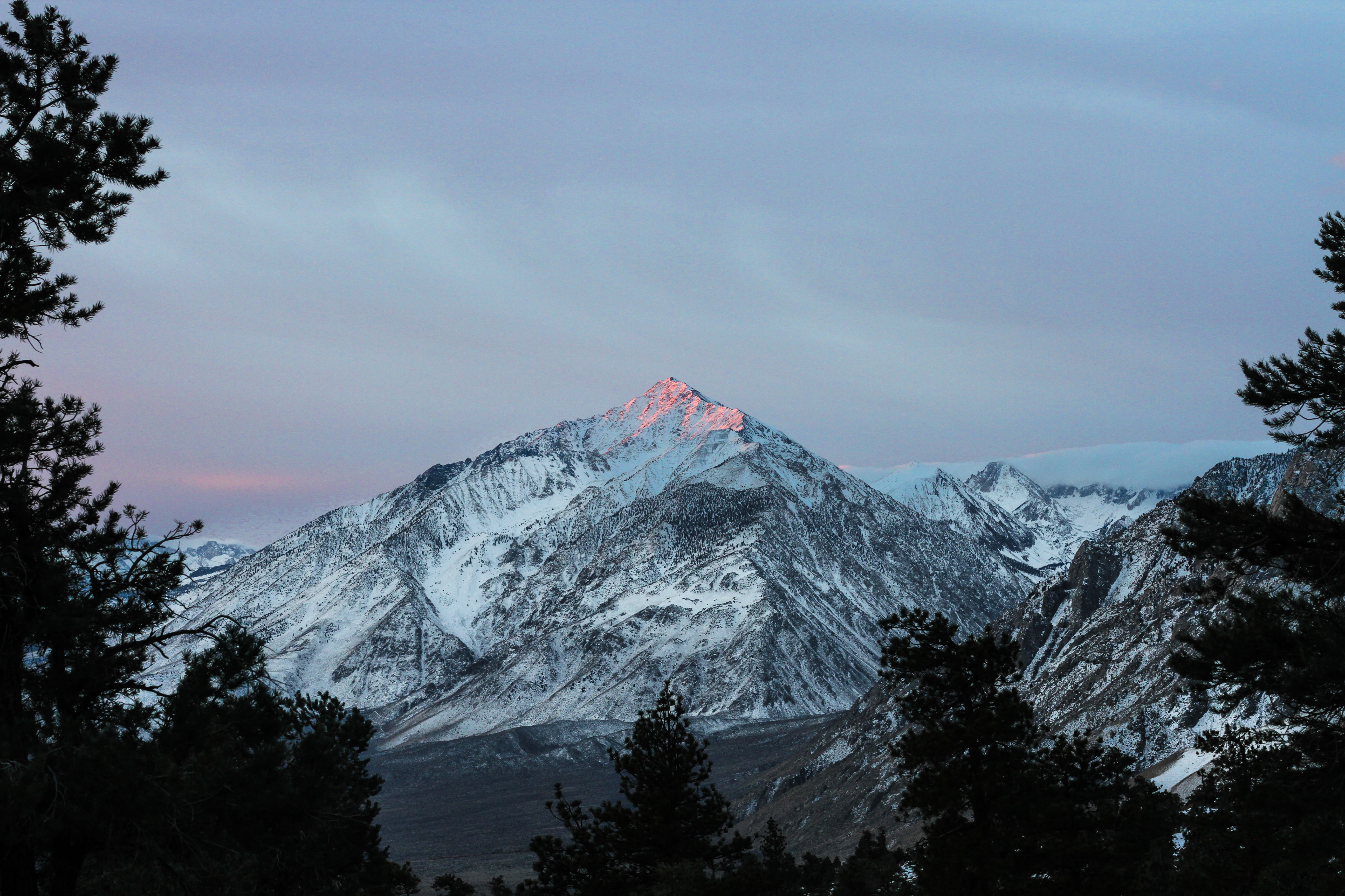 The peak of the tall Mount Whitney bathed in red sunshine during sunset