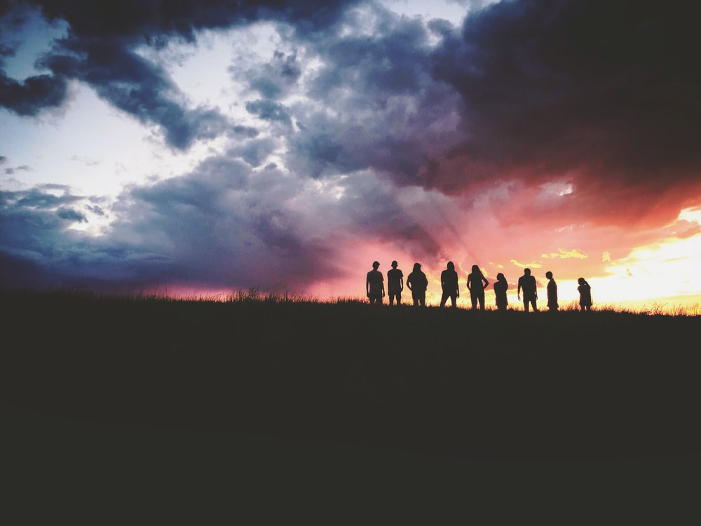 silhouette of nine persons standing on the hill