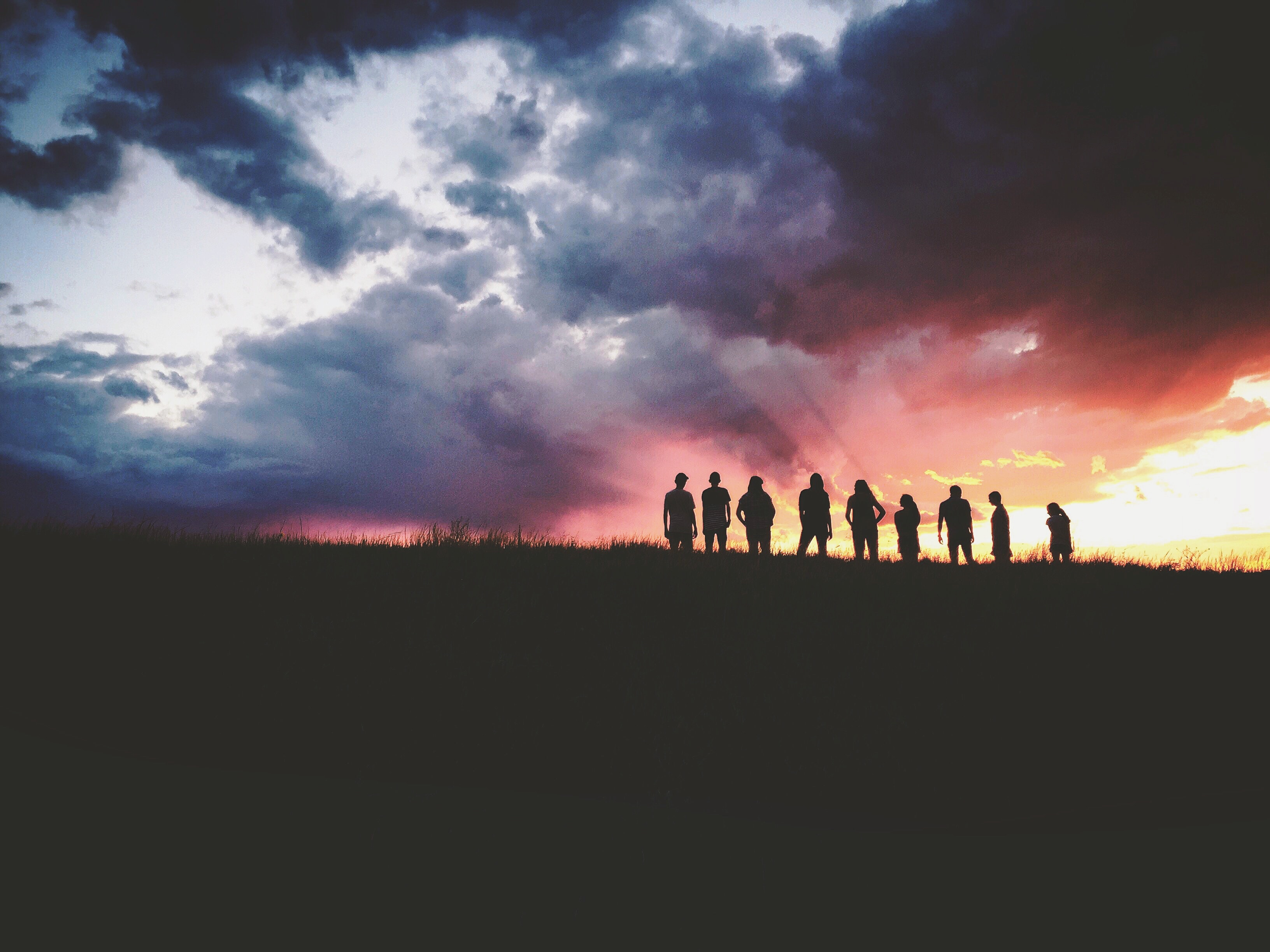 Silhouette of a group of friends standing atop a hill in the Black Forest watching the sunset