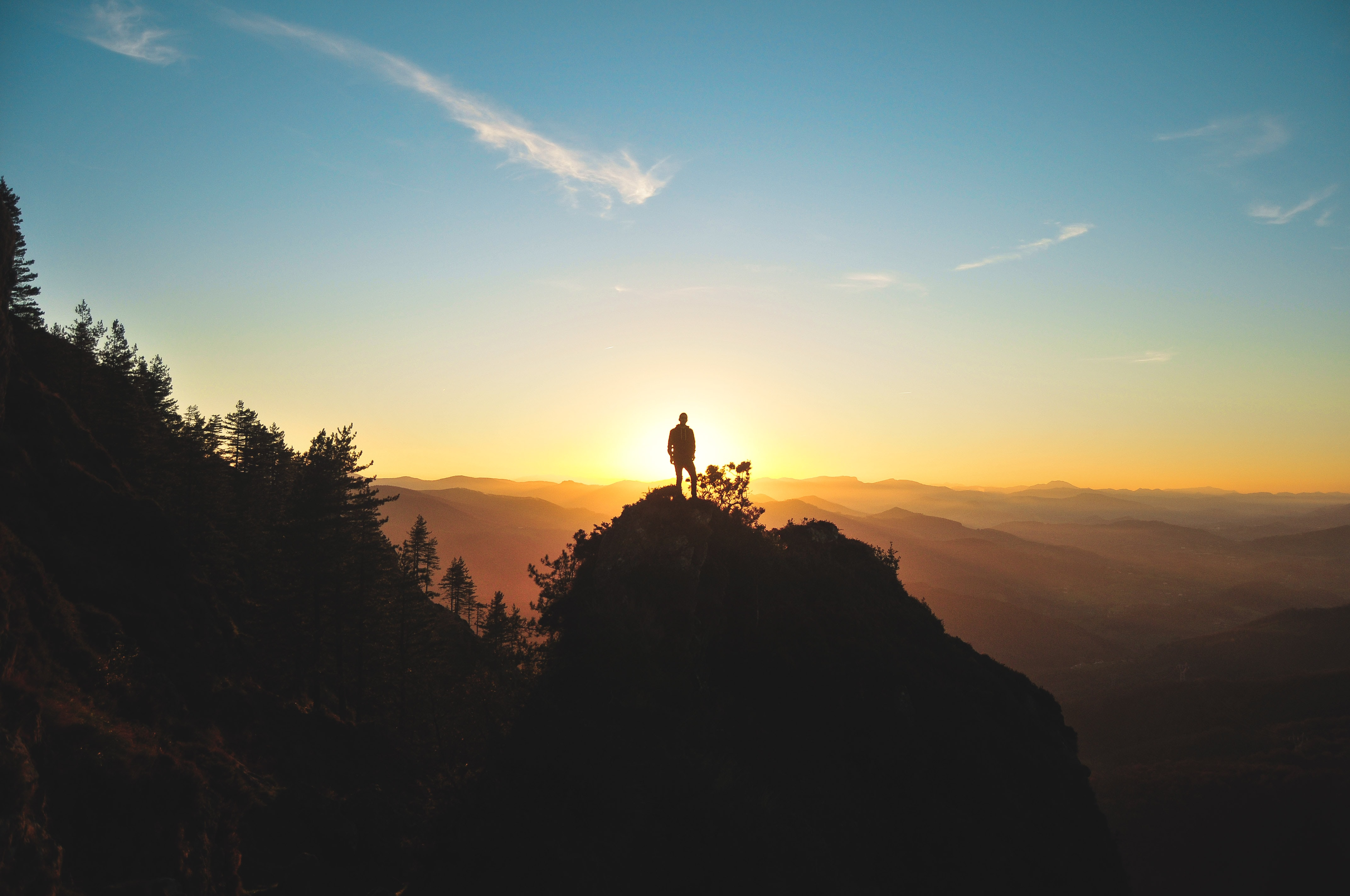 A man standing on a tall rock silhouetted against the setting sun