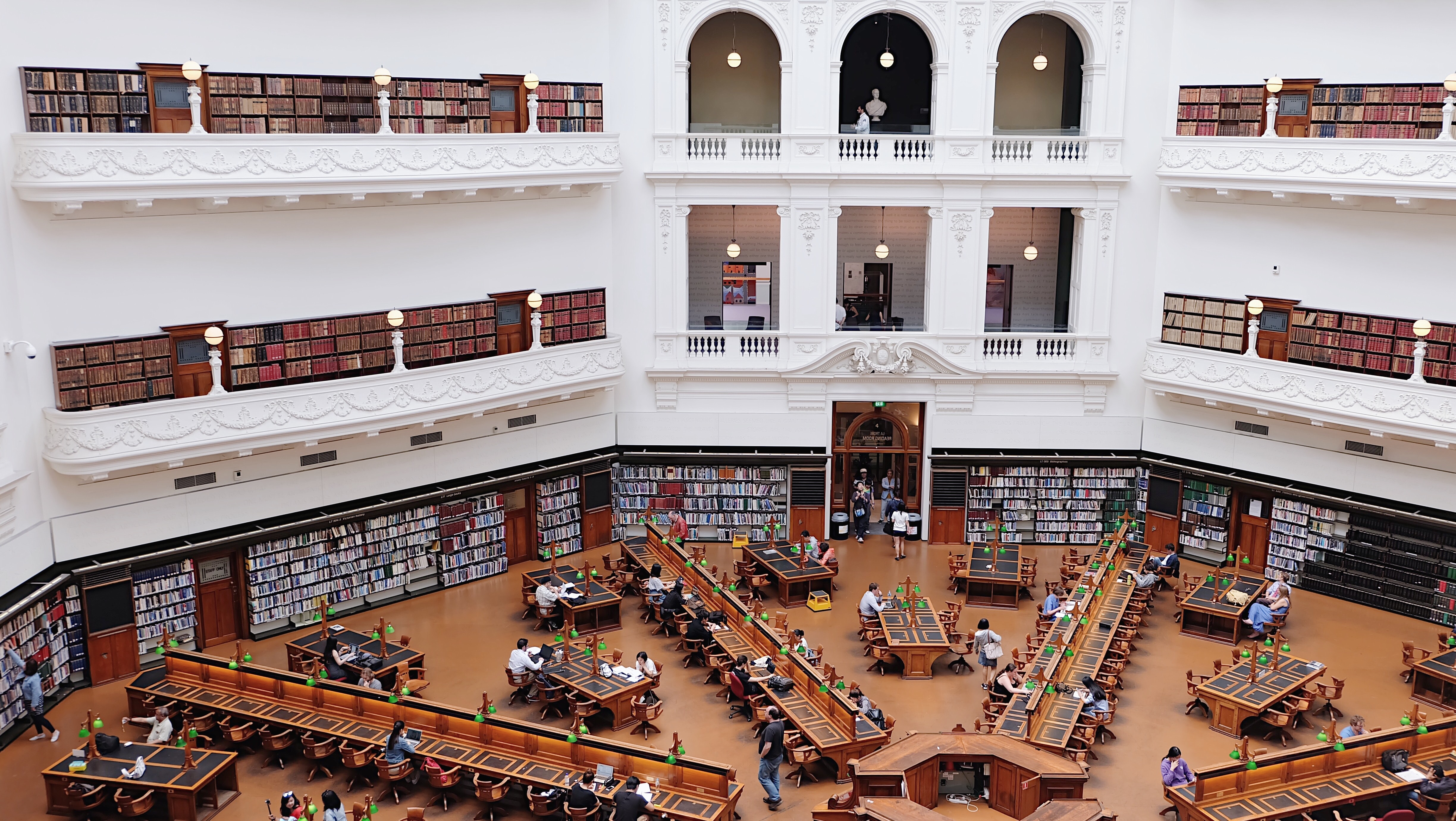 Interior view of the State Library of Victoria with bookcases and people sitting at desks