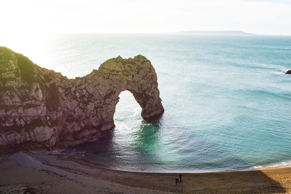 aerial view of beach with arch rock formation
