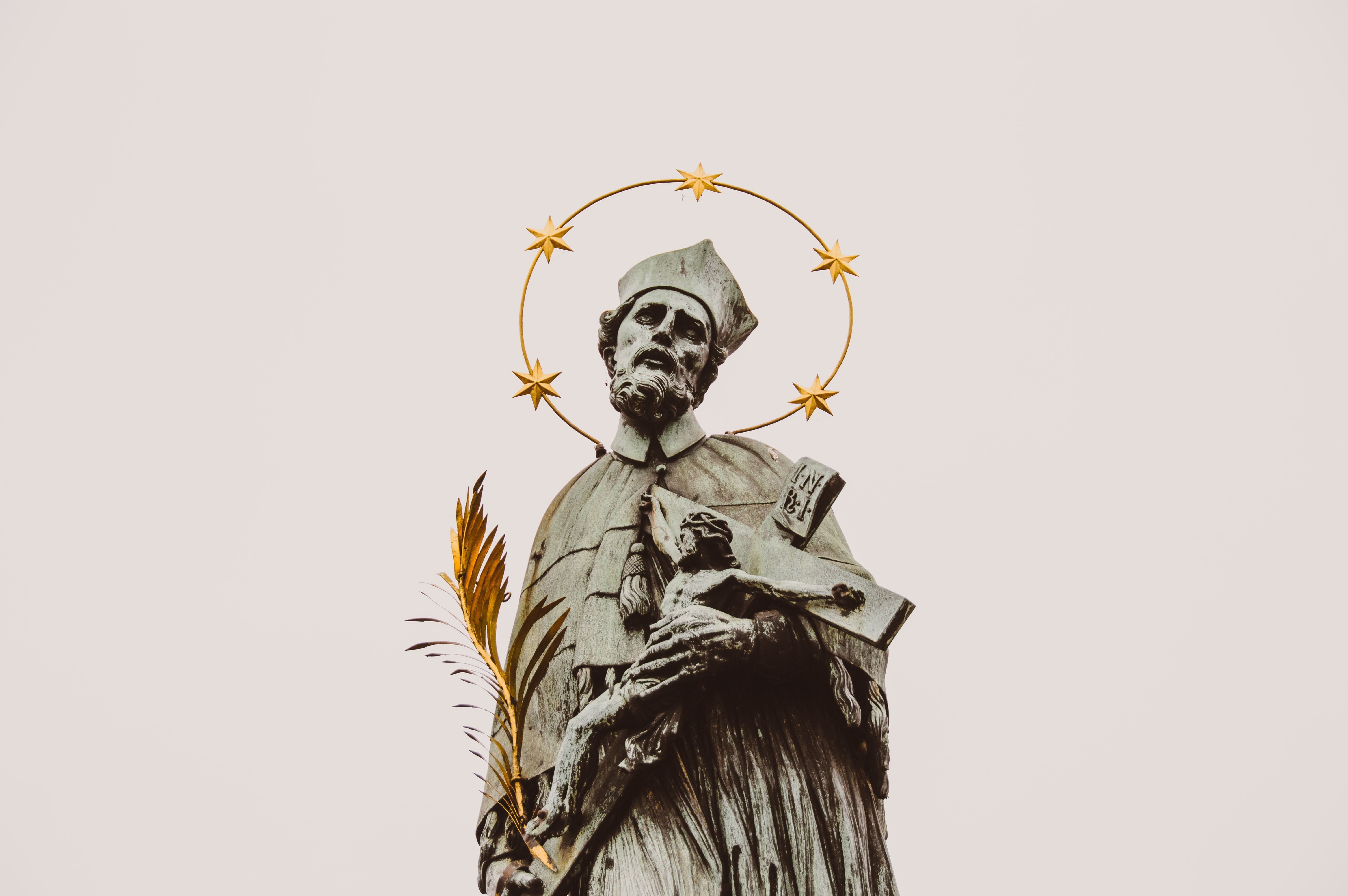 Stone statue of a saint and crucifix with a gold halo in Prague