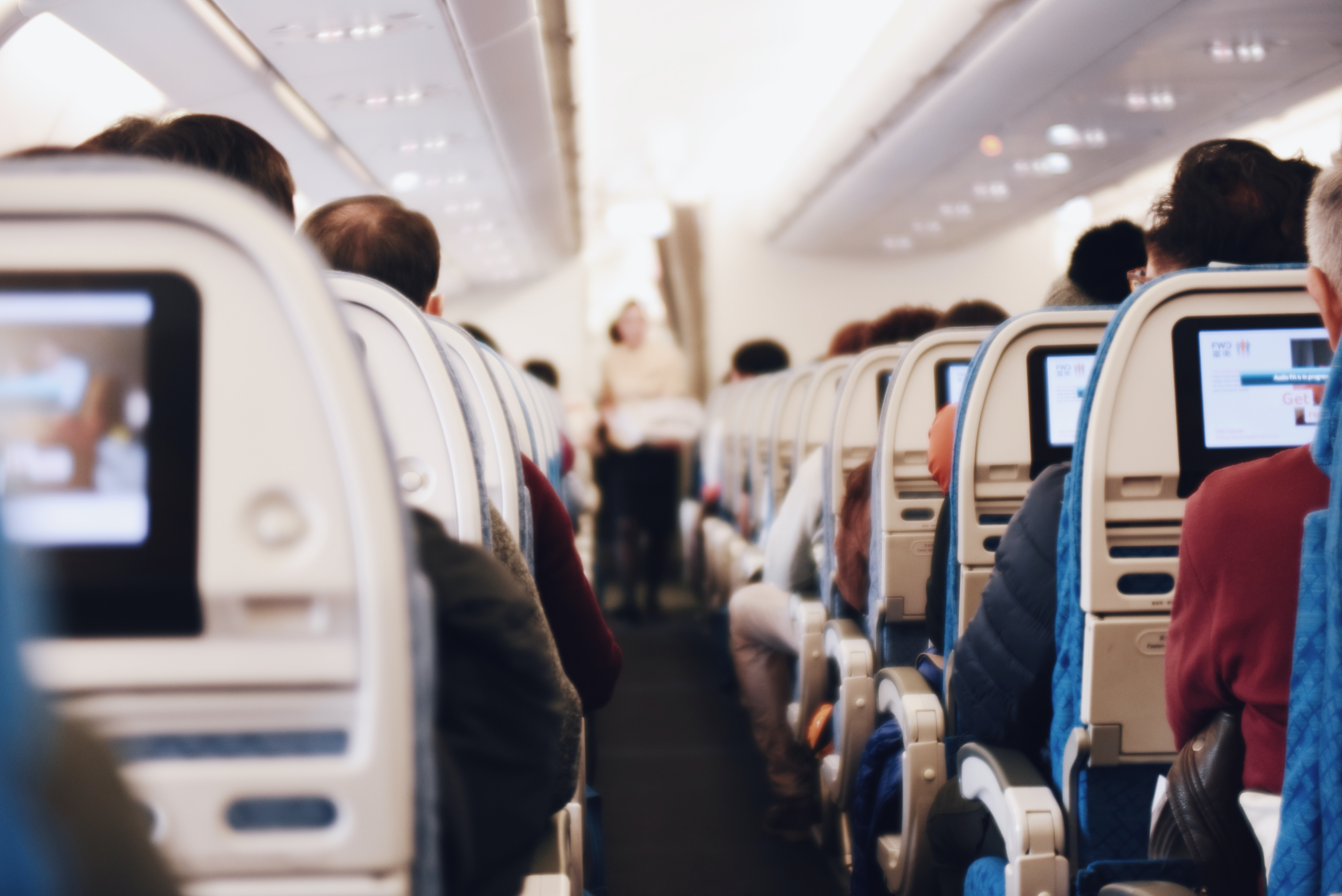 A view of the airplane aisle with a flight attendant carrying a tray