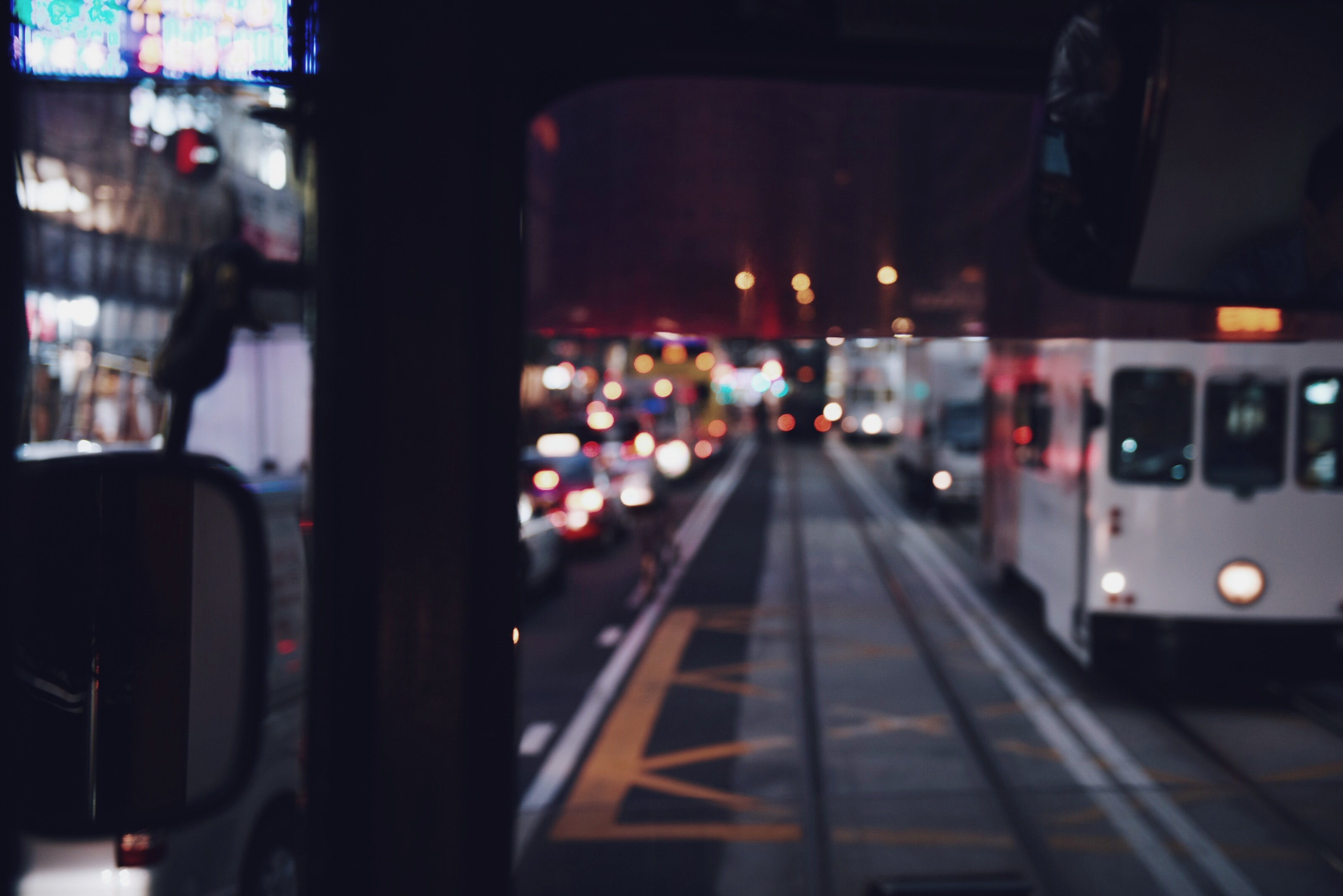 Buses and trains drive past the station on a busy night in the city