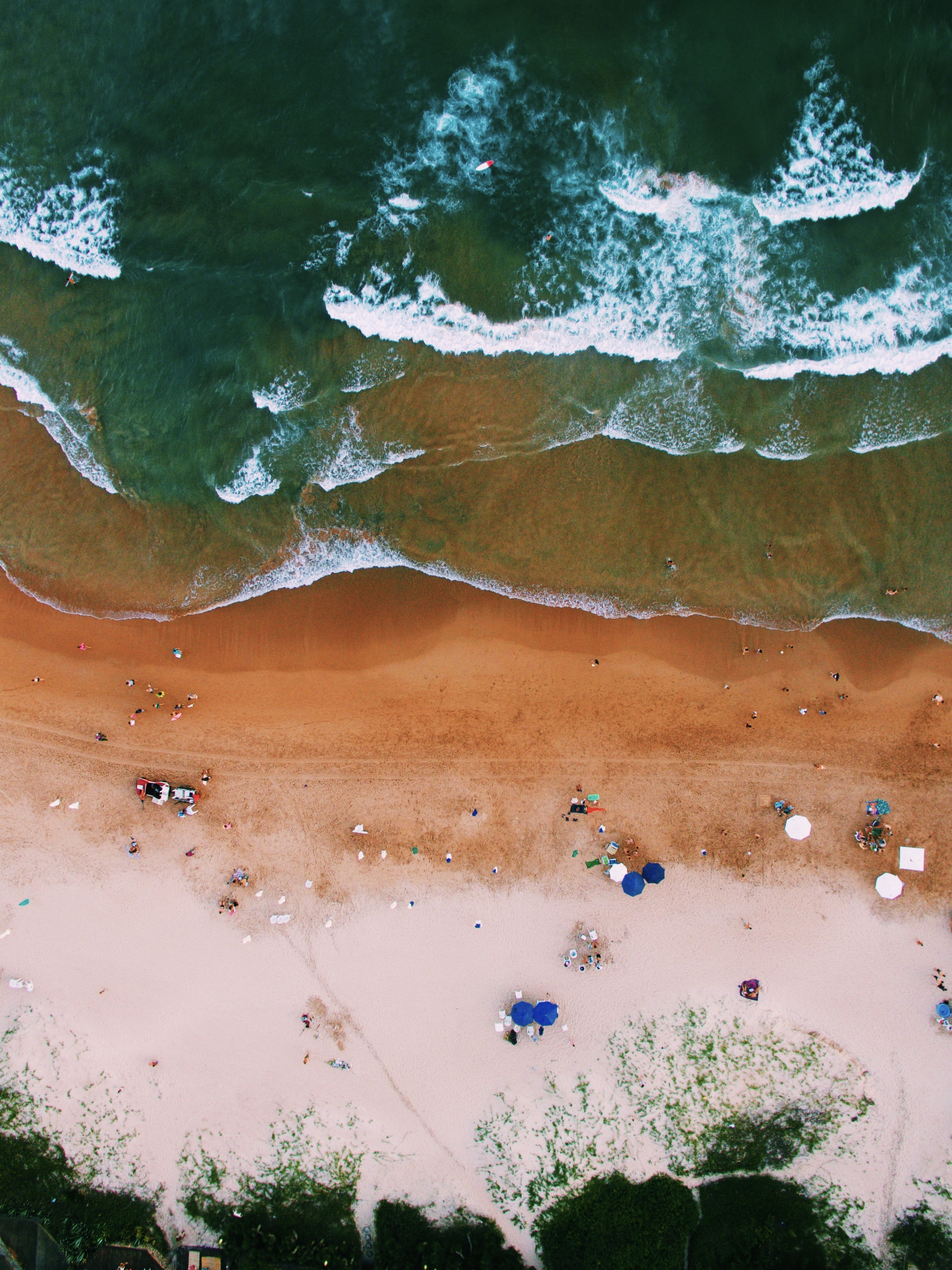 An aerial shot of waves breaking on a wet golden beach with tourists, their umbrellas and deck chairs