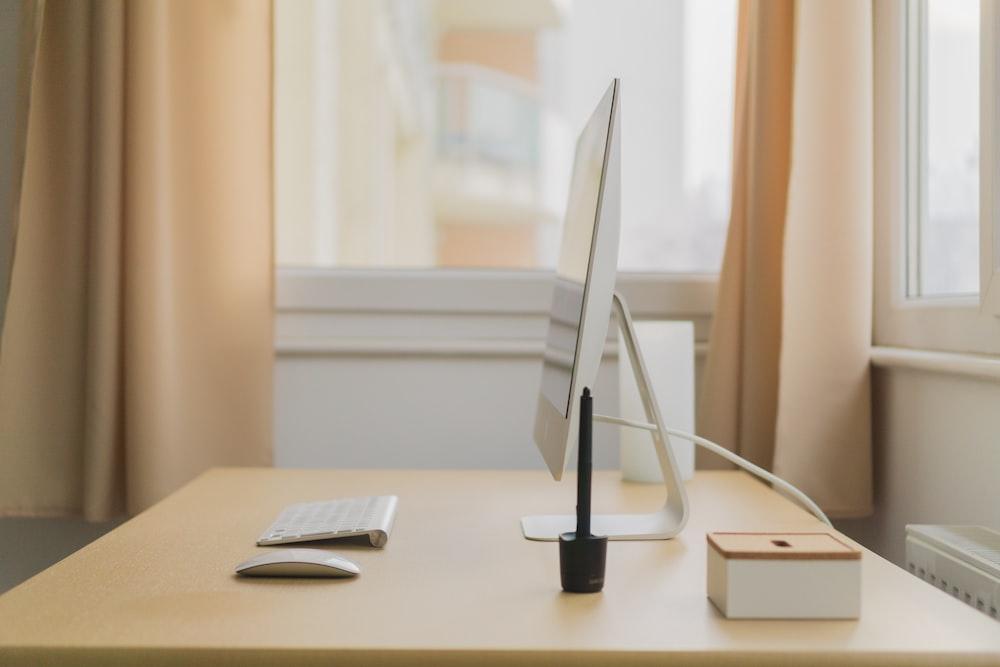 Apple iMac on wooden desk near window