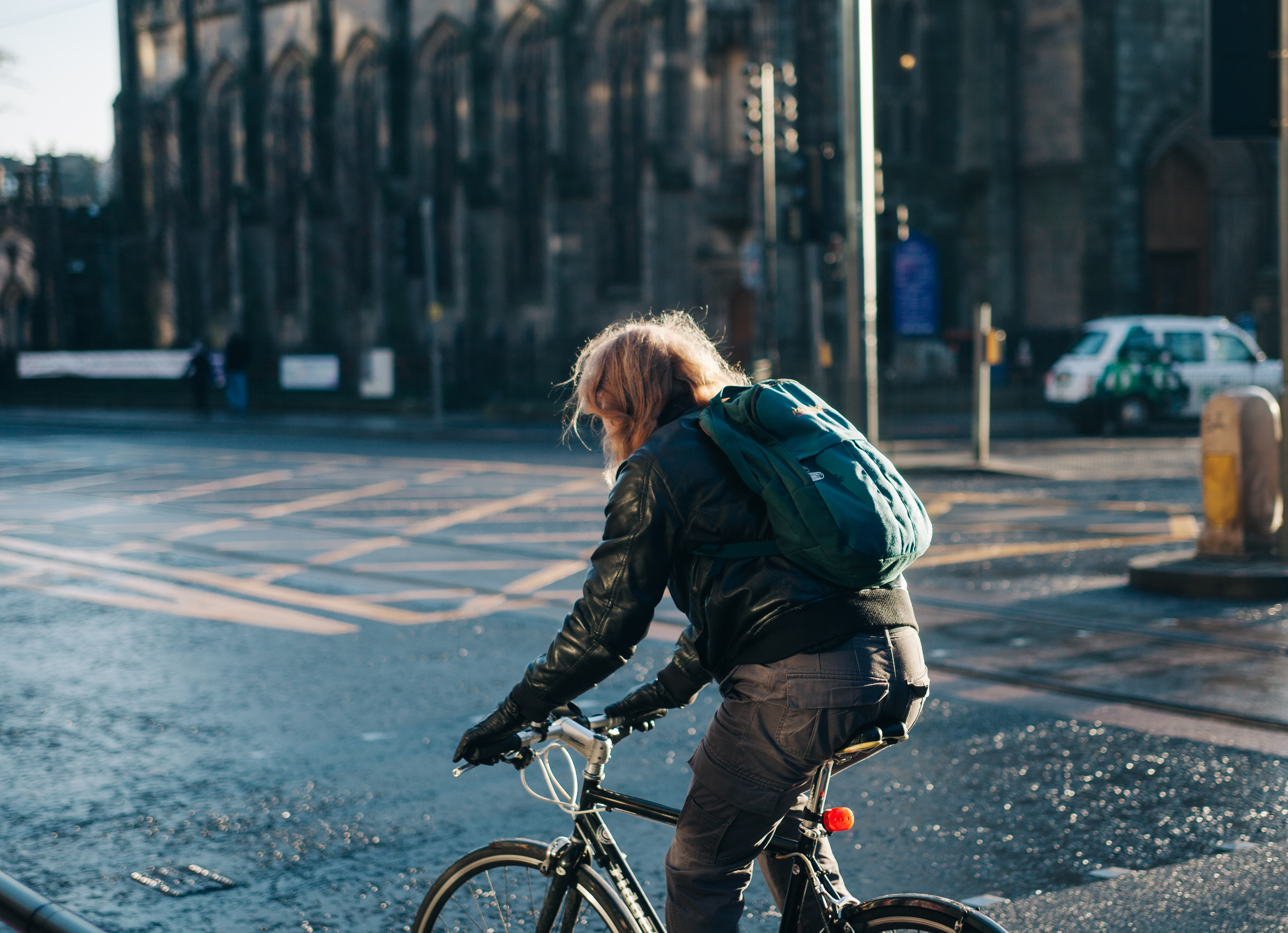 A person wearing a leather jacket and backpack riding a bicycle on a road in Edinburgh