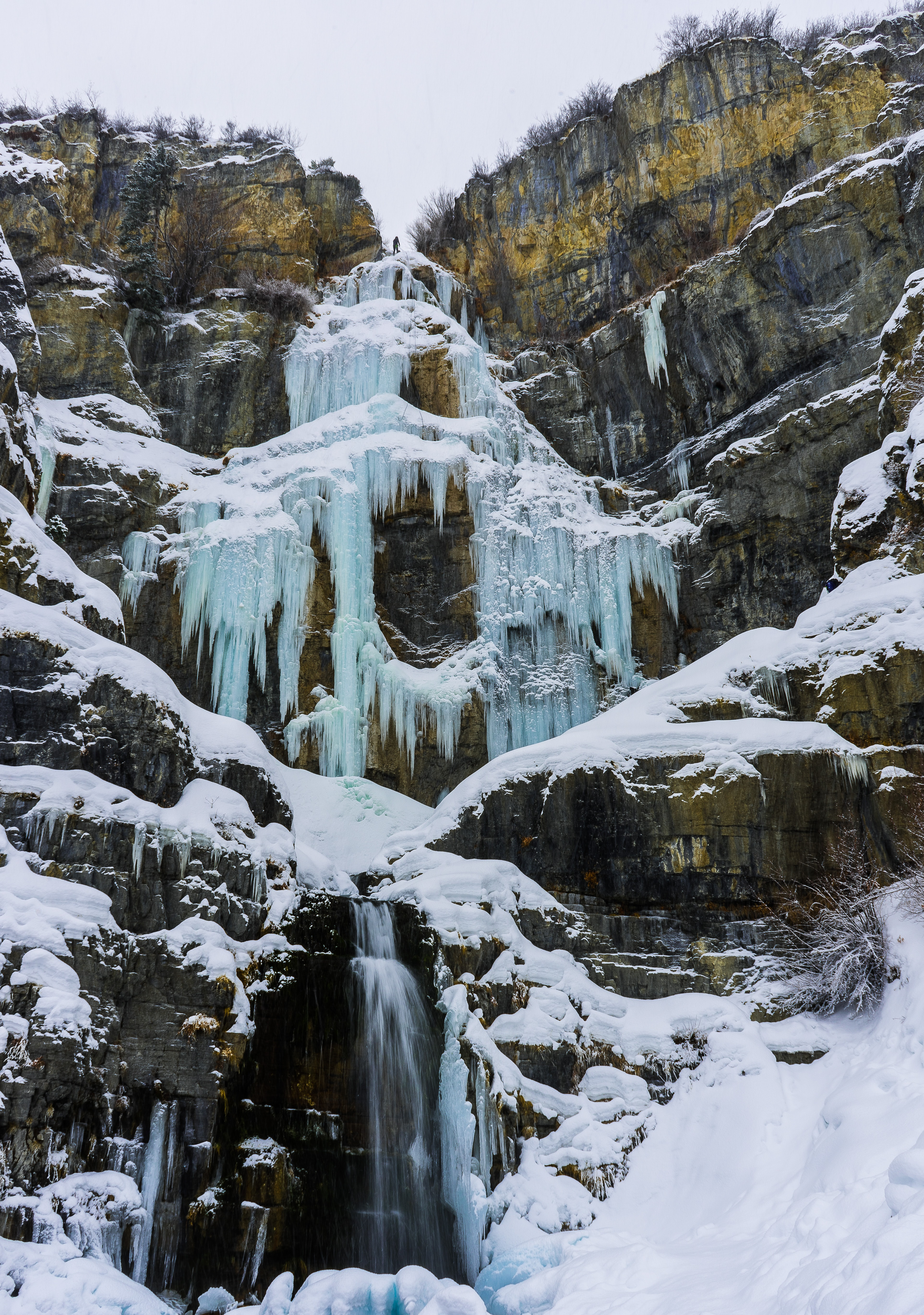 Frozen icy waterfall cascades down rocky cliff