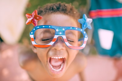 boy wearing american flag print eyeglasses sticking his mouth open independence day teams background
