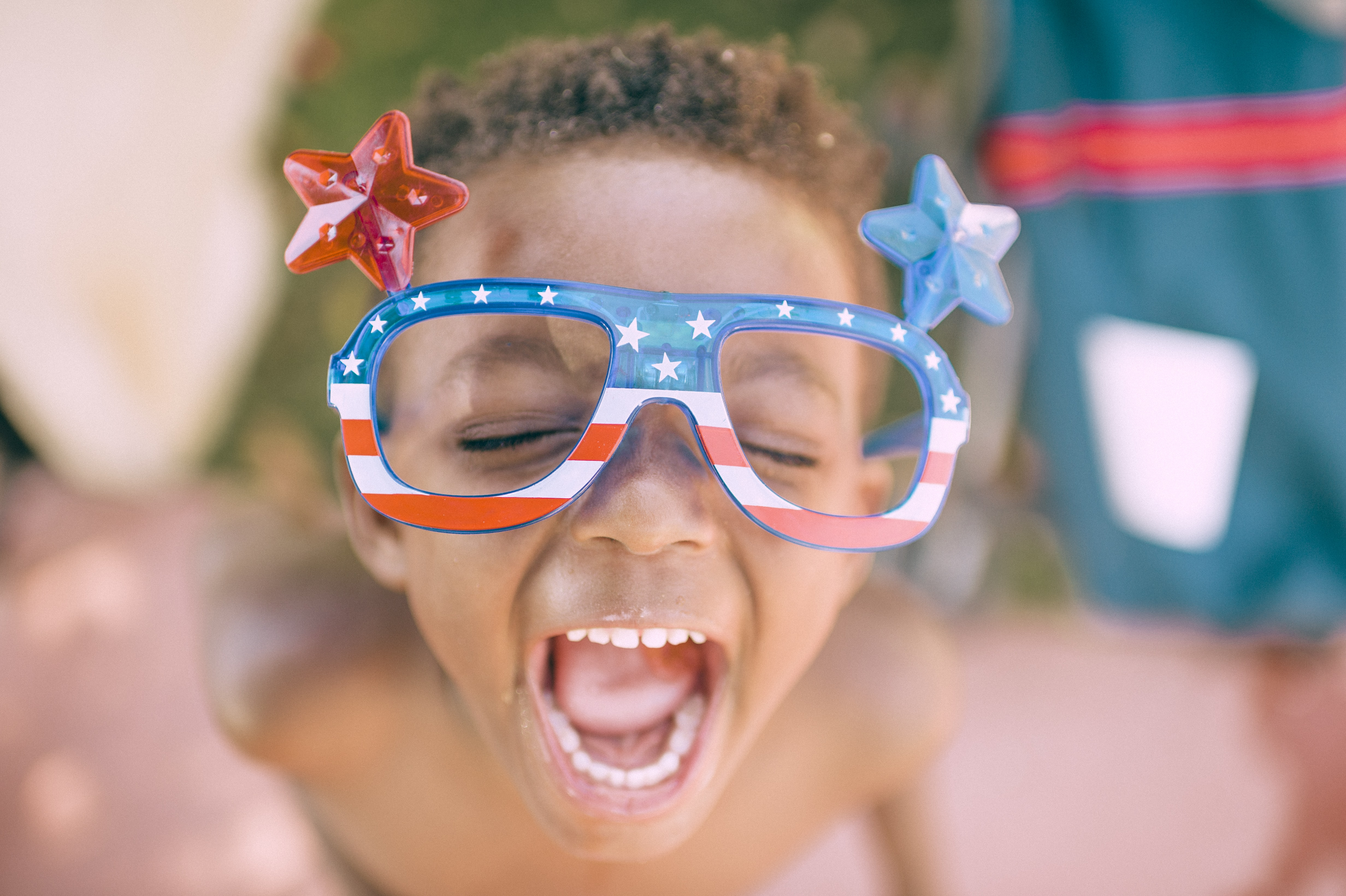A child making a funny face while wearing goofy American patriotic glasses with plastic stars