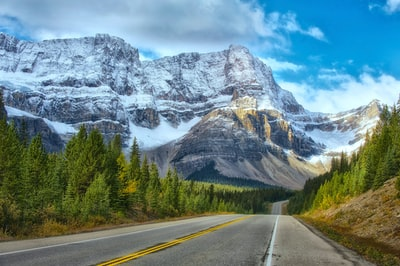 landscape photography of concrete road near the mountains banff teams background