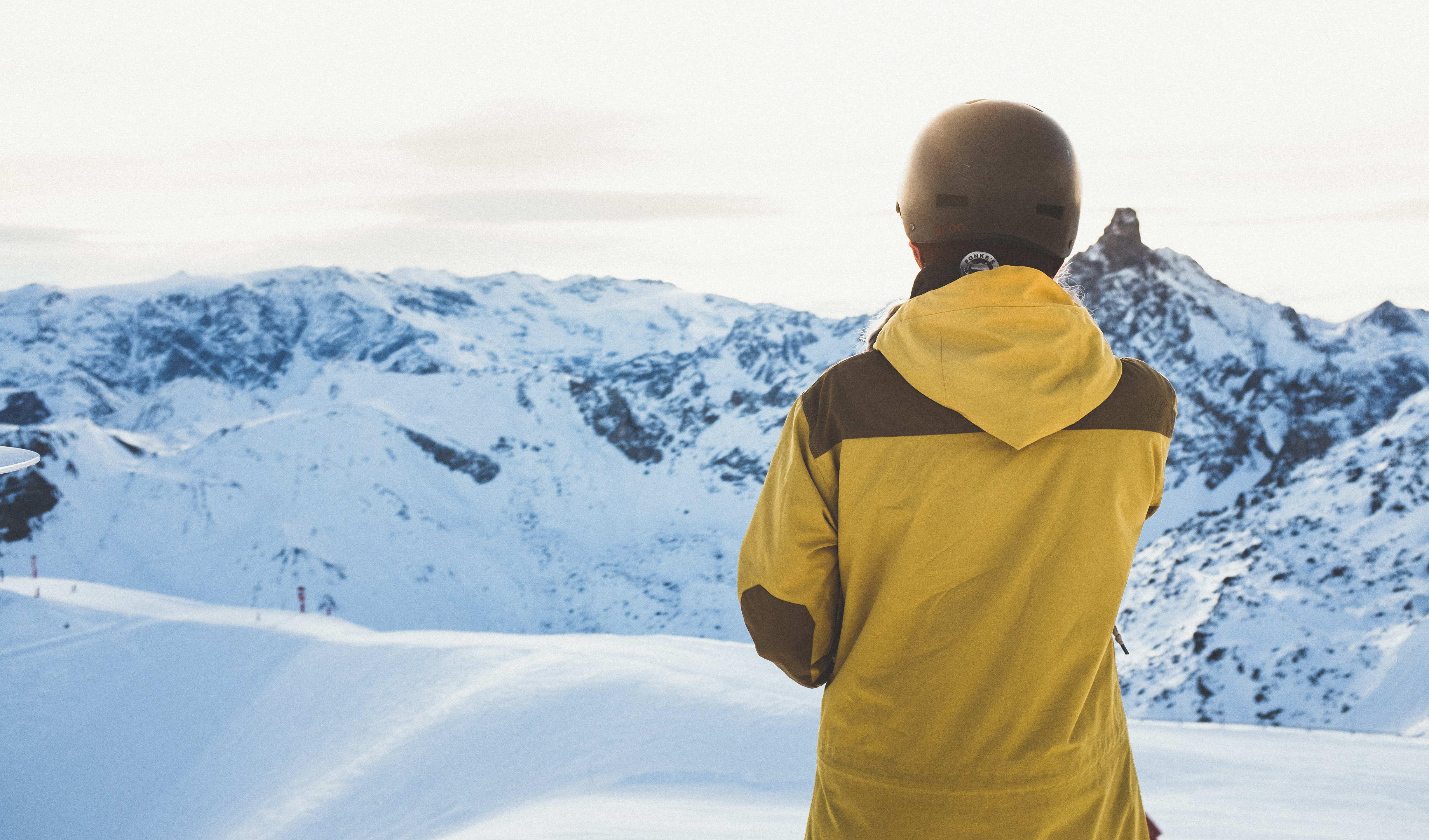 A person in a jacket and helmet looks toward snowy mountains in the distance in Méribel