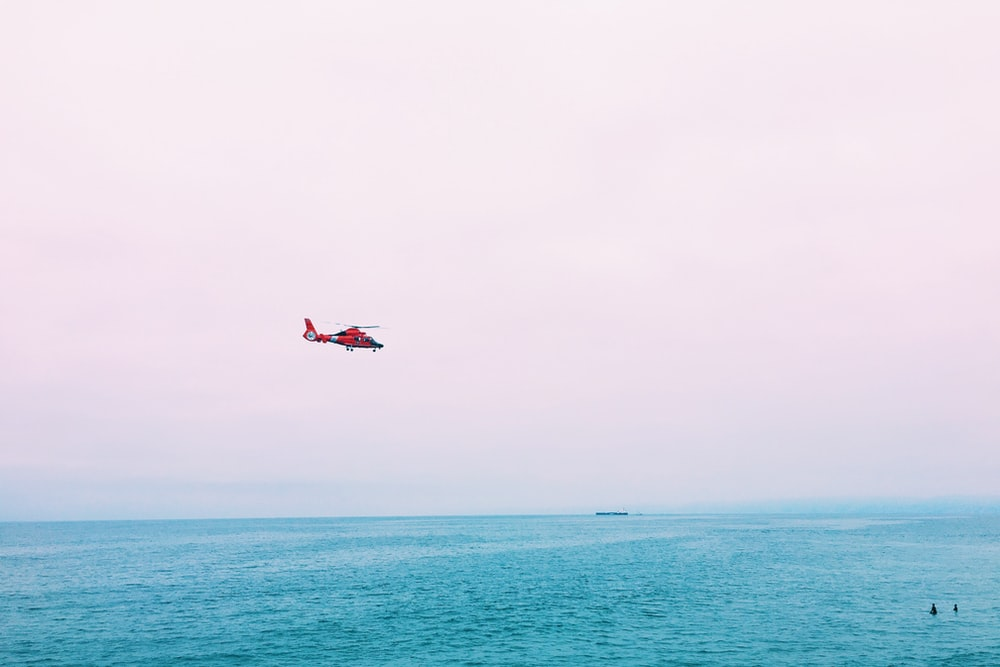 red plane on mid air above sea
