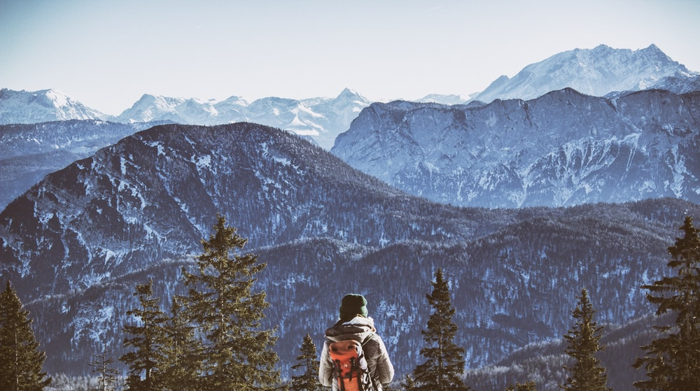 person wearing backpack near mountain during daytim