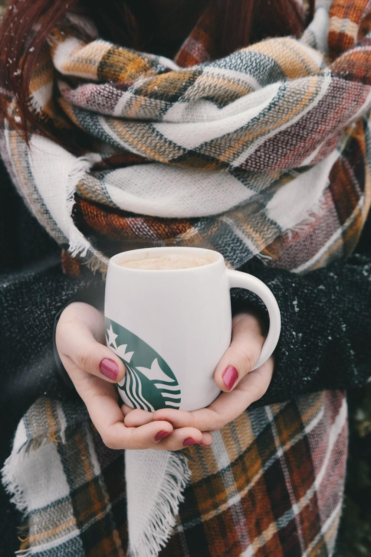 person holding white and green Starbucks ceramic mug