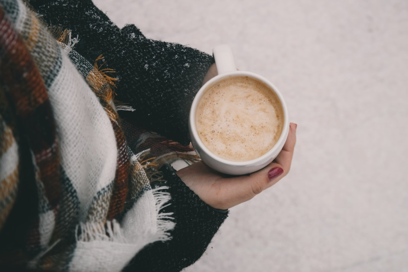 view from above of white woman holding a cup of cappuccino, she's dressed for winter and only her arms and hands are visible, with snowy ground as the background