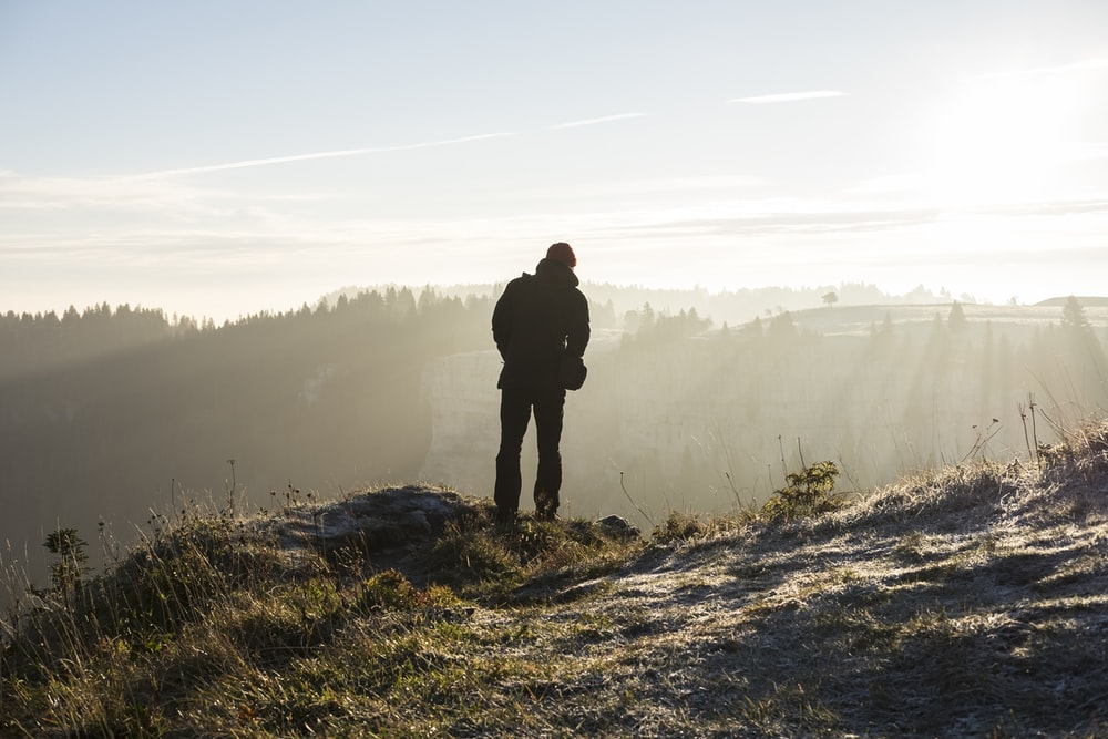 man standing on cliff near trees during daytime
