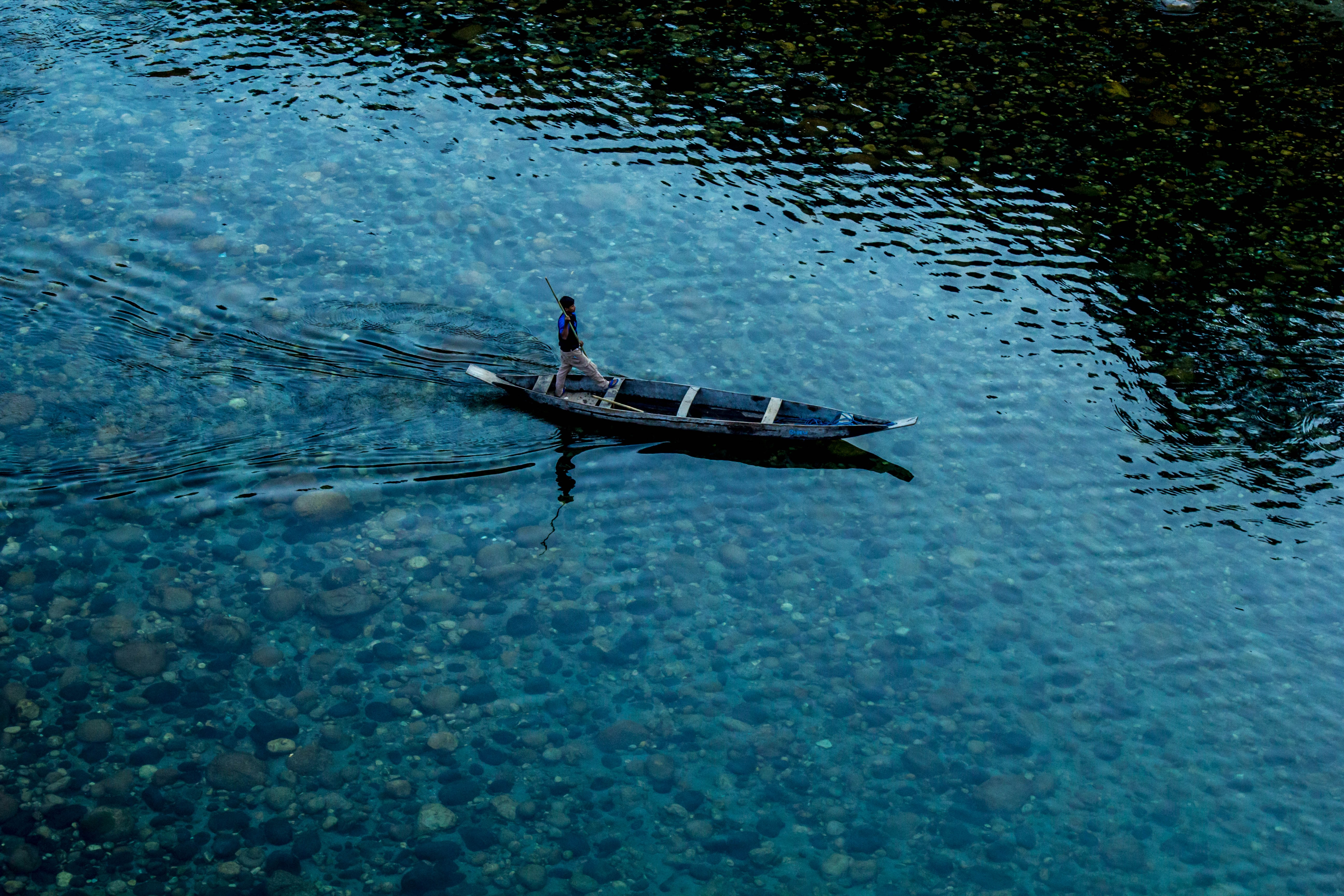 top view photo of man riding wooden boat on calm body of water