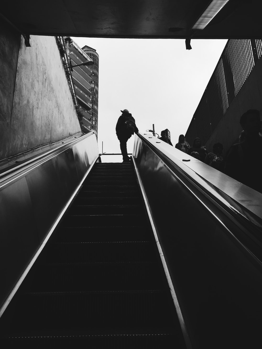 silhouette of person standing beside escalator during daytime