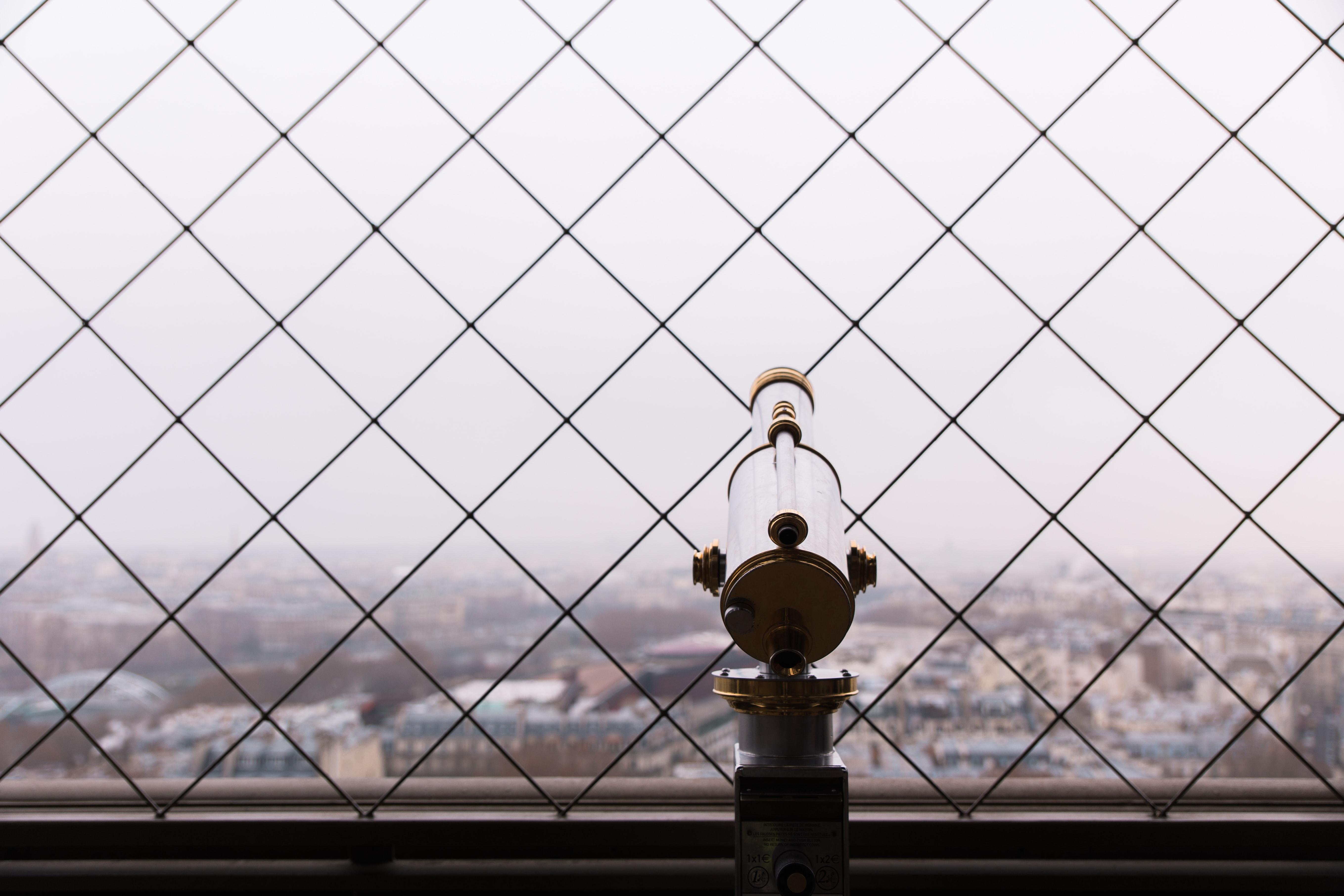 Telescope viewfinder with Paris cityscape in the background
