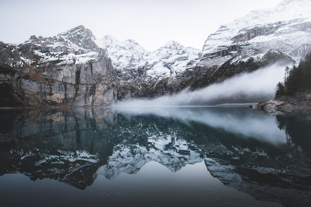snow covered mountain near reflecting on water during daytime