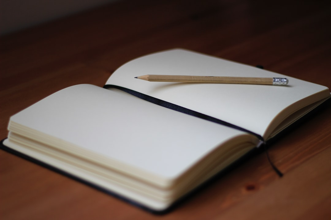 A pencil on the blank pages of an open notebook