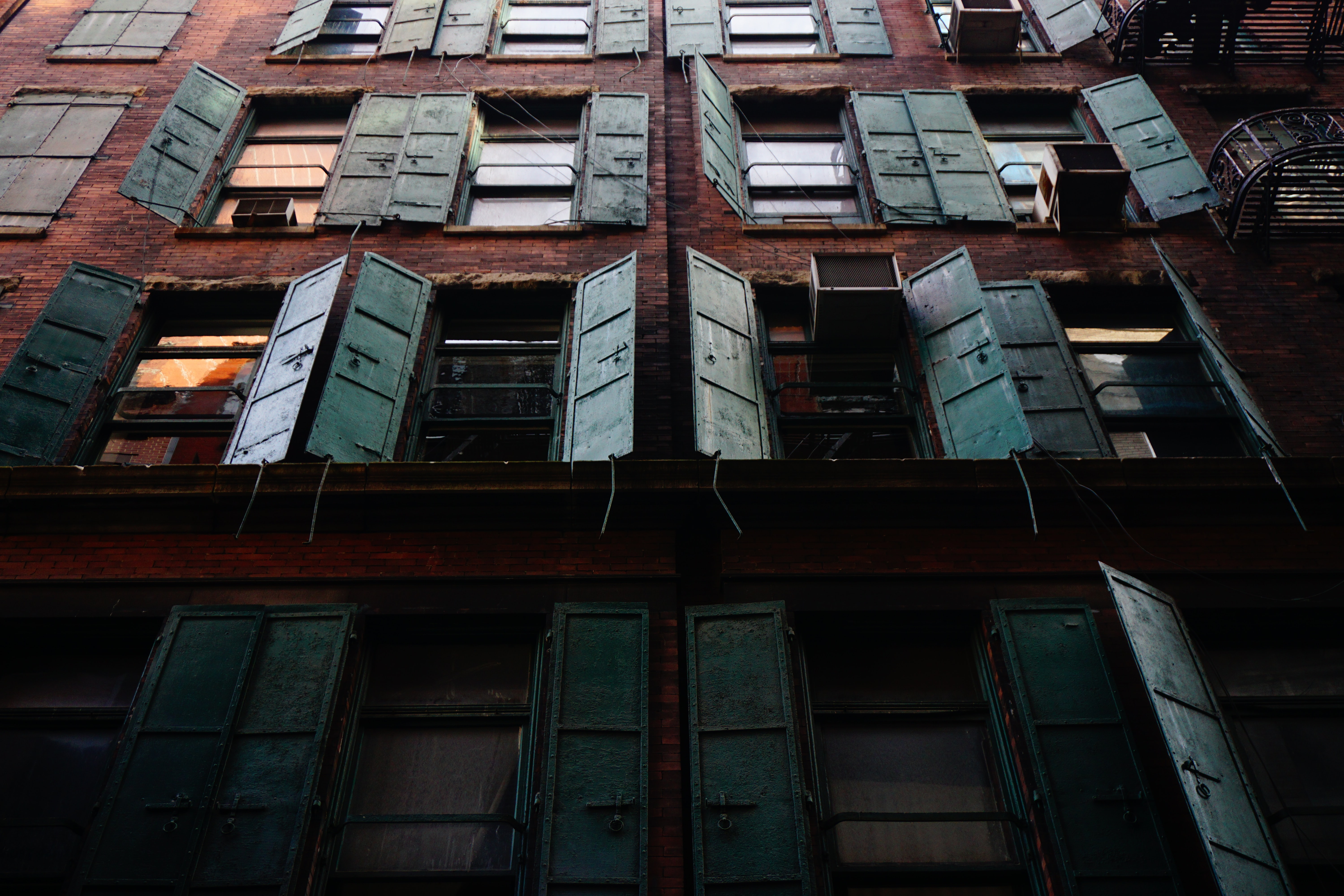 An old brick building with rustic window shutters in New York.