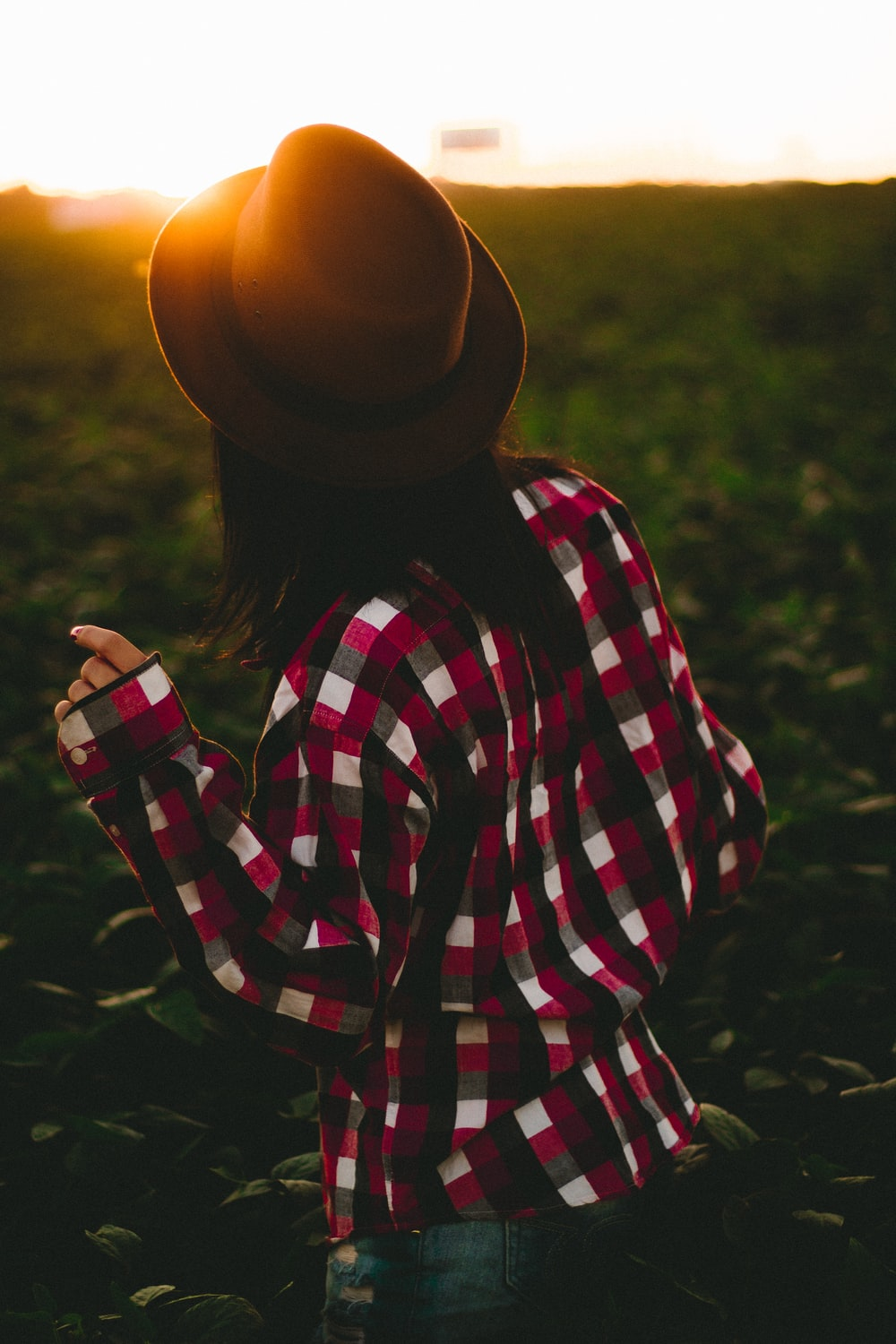 woman wearing hat and checked shirt on green grass