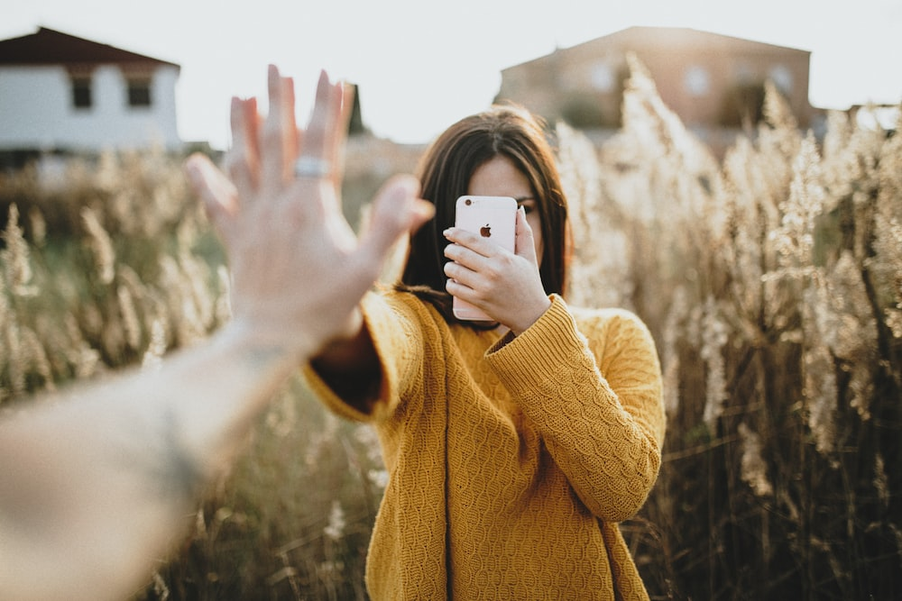 A woman is high-fived while holding her phone in a field.