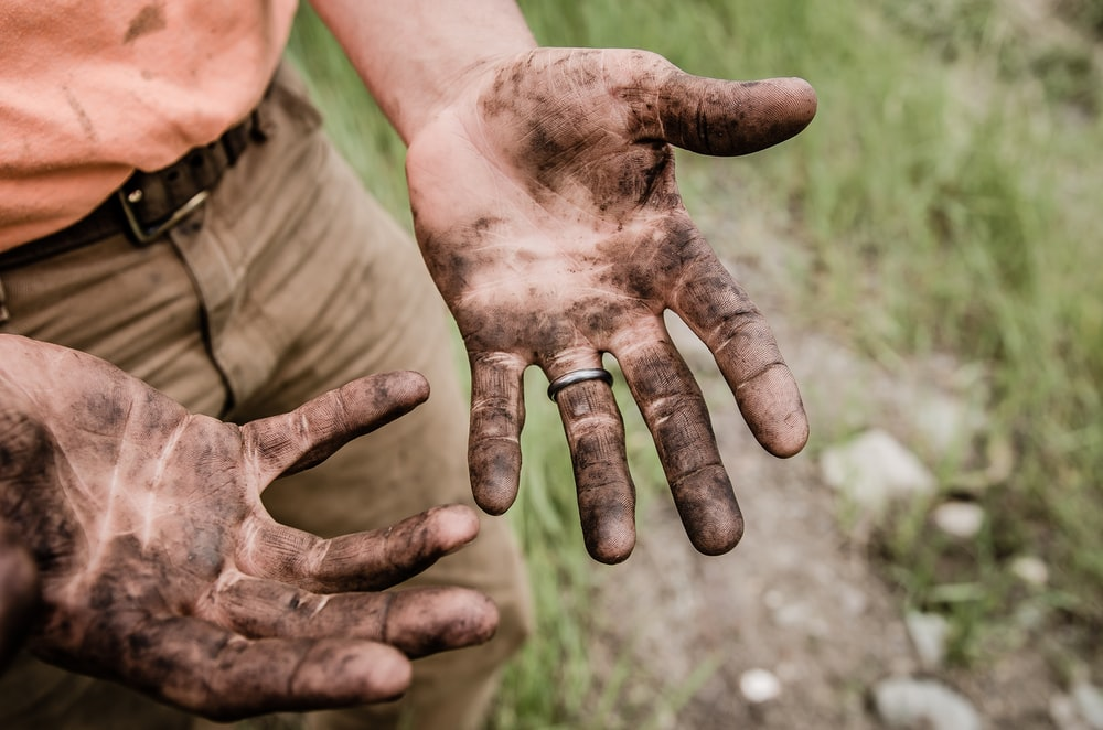 A man with his hands covered with mud
