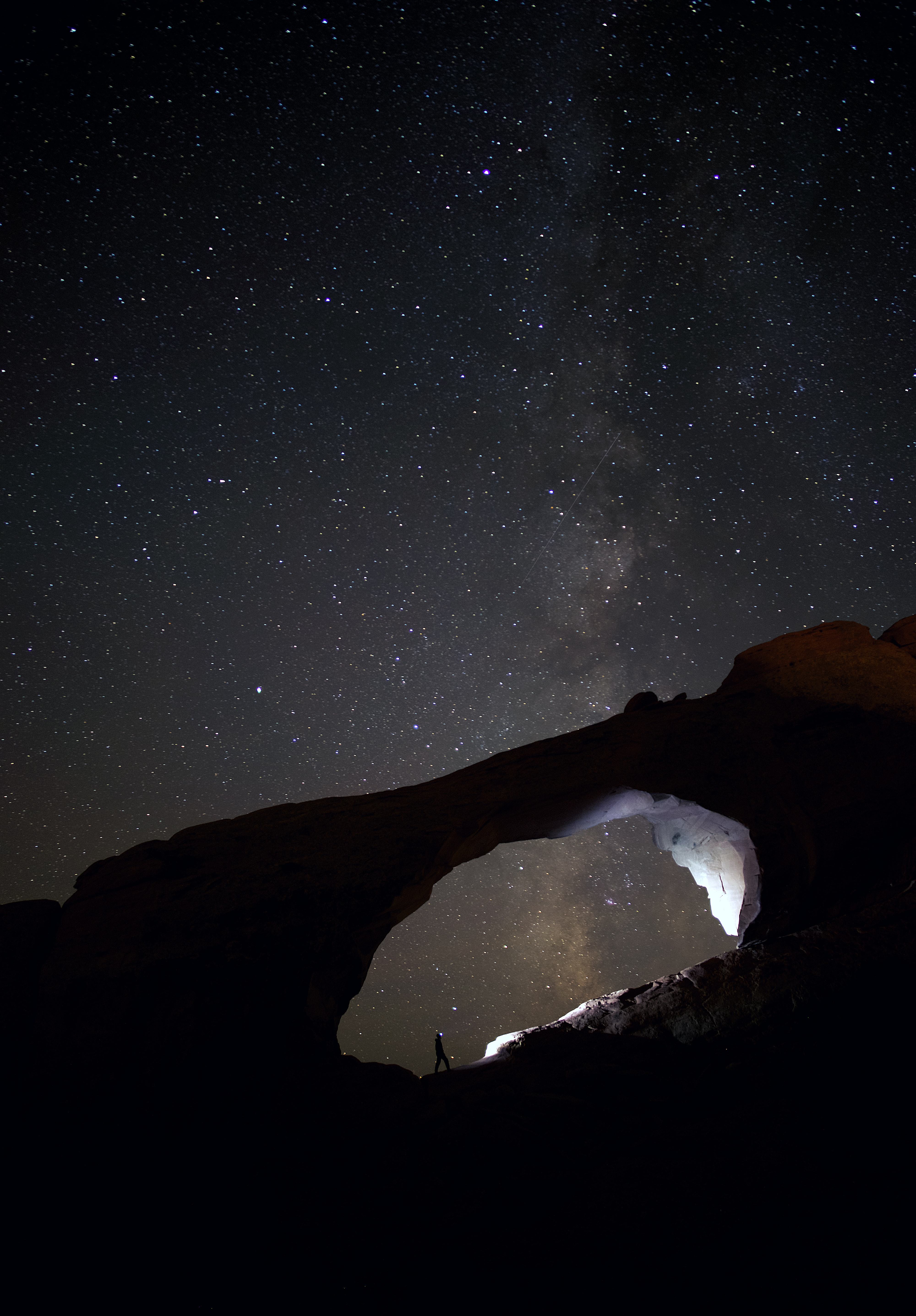 silhouette photo of person stand on rocks during nighttime