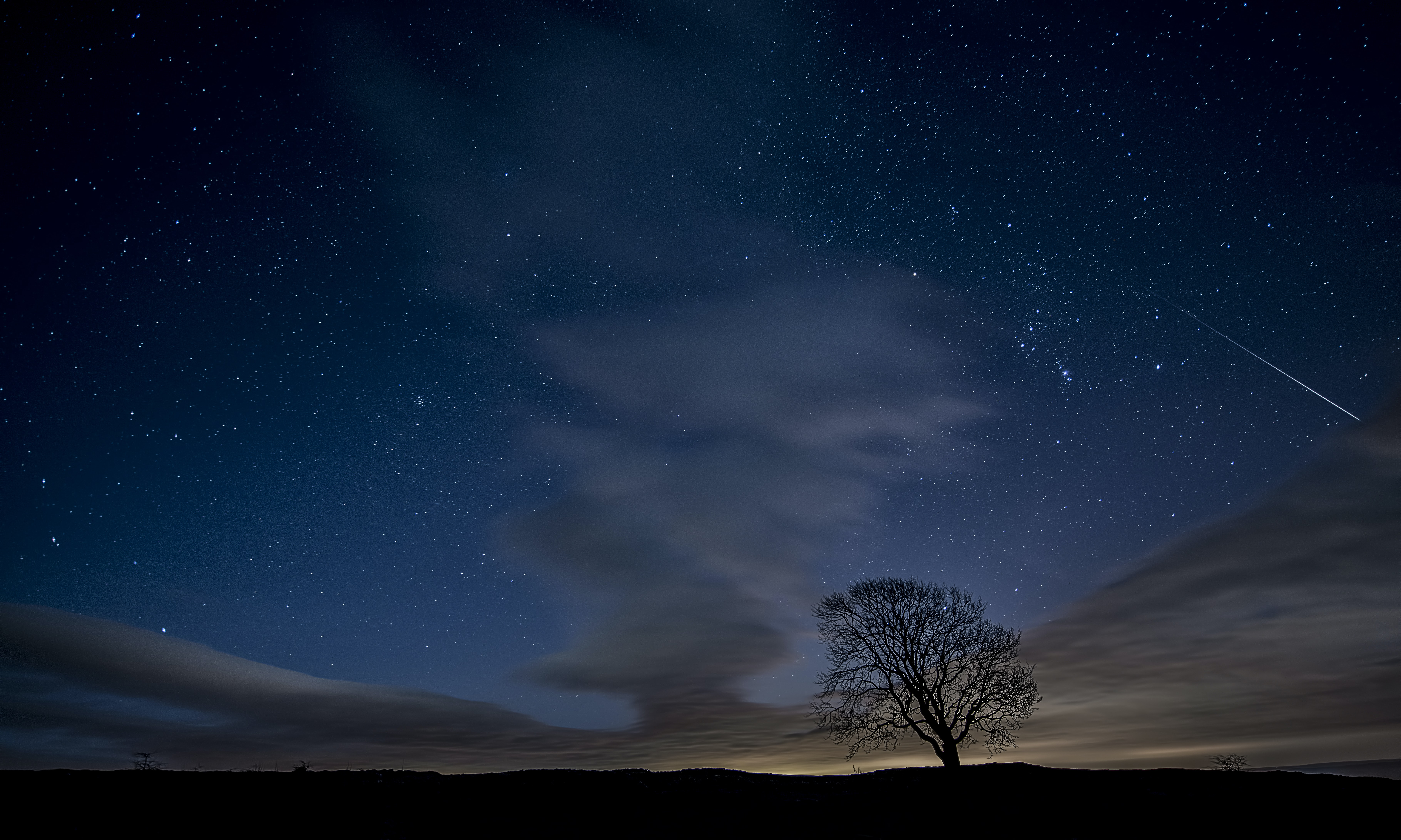 A night-time background featuring a blue sky with gusty dark clouds in Malham Cove
