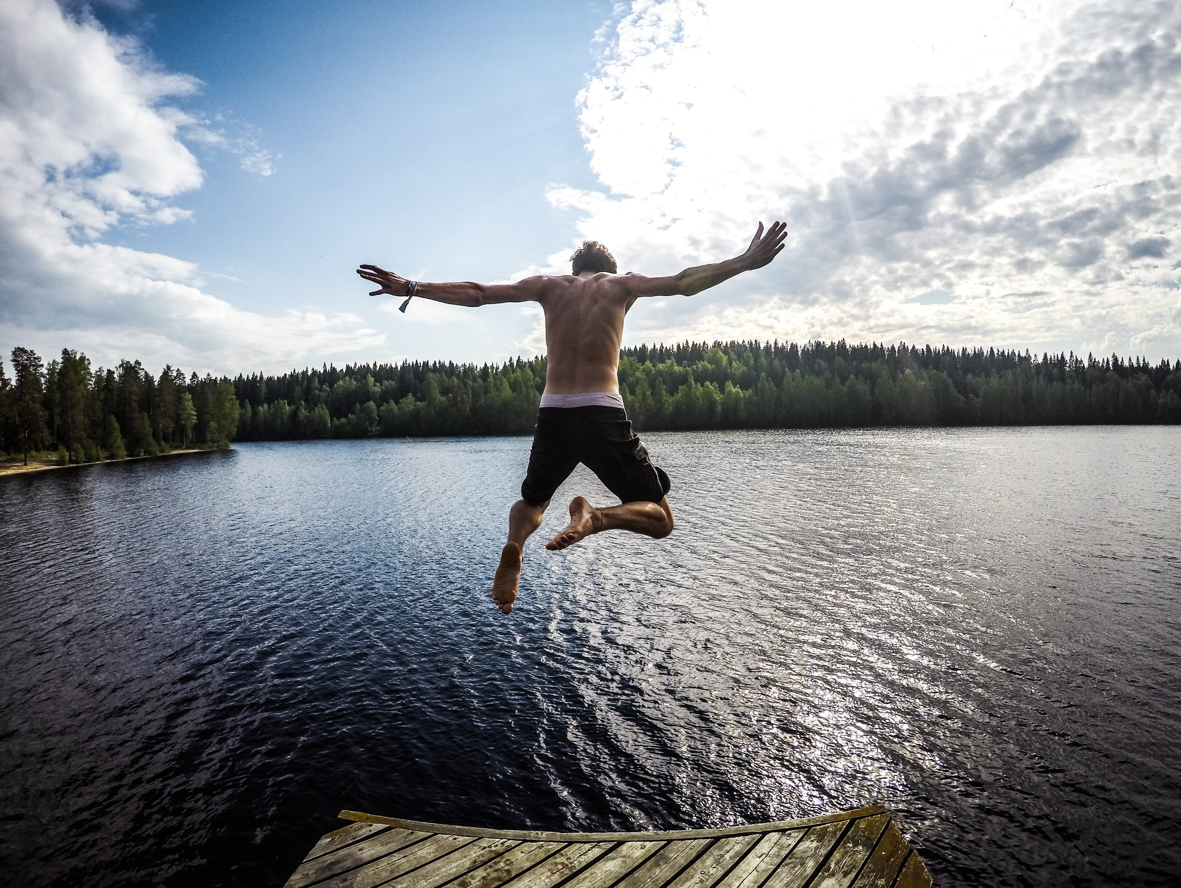 A man leaping into a lake from a pier