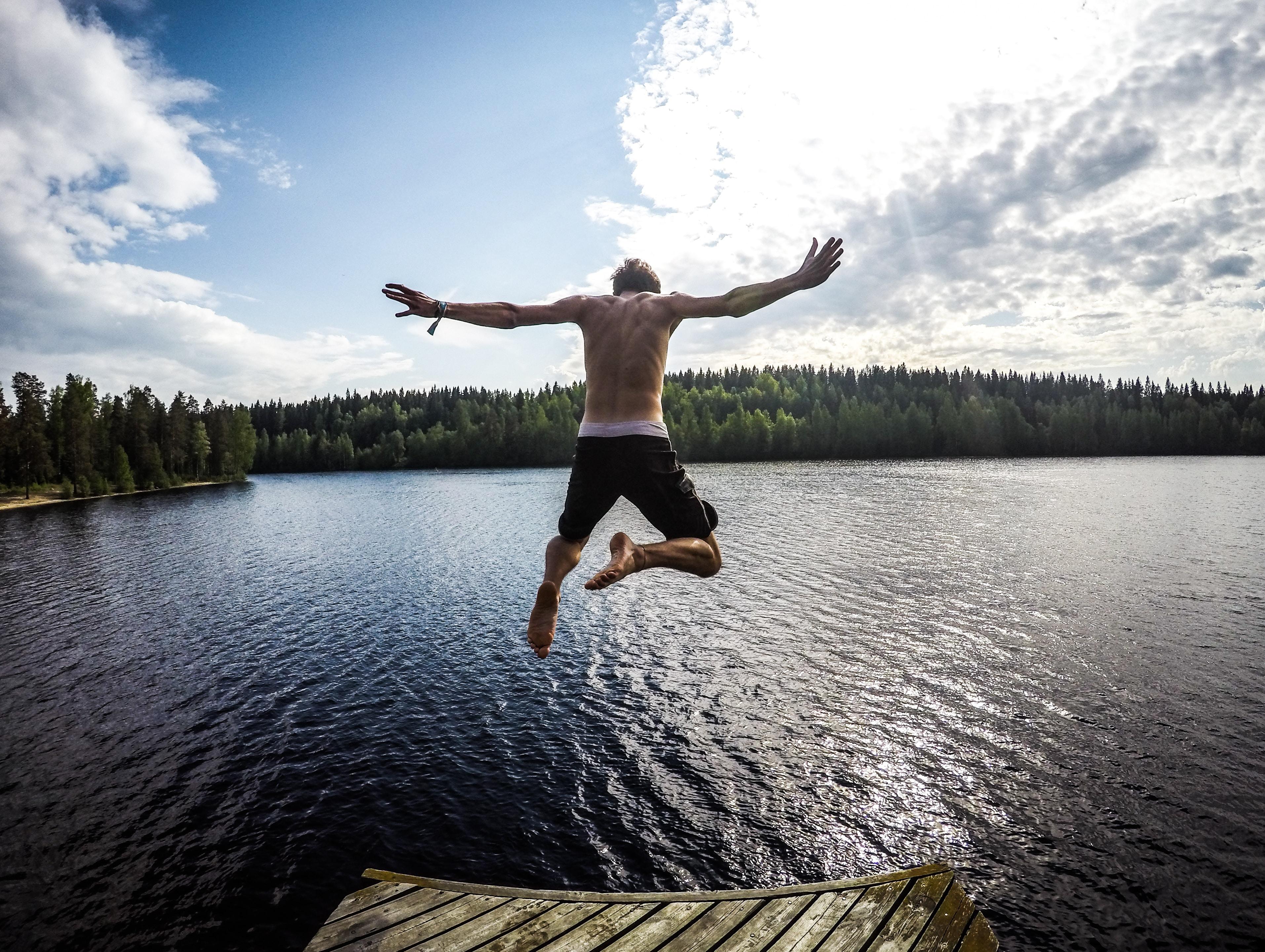 man jumping through body of water