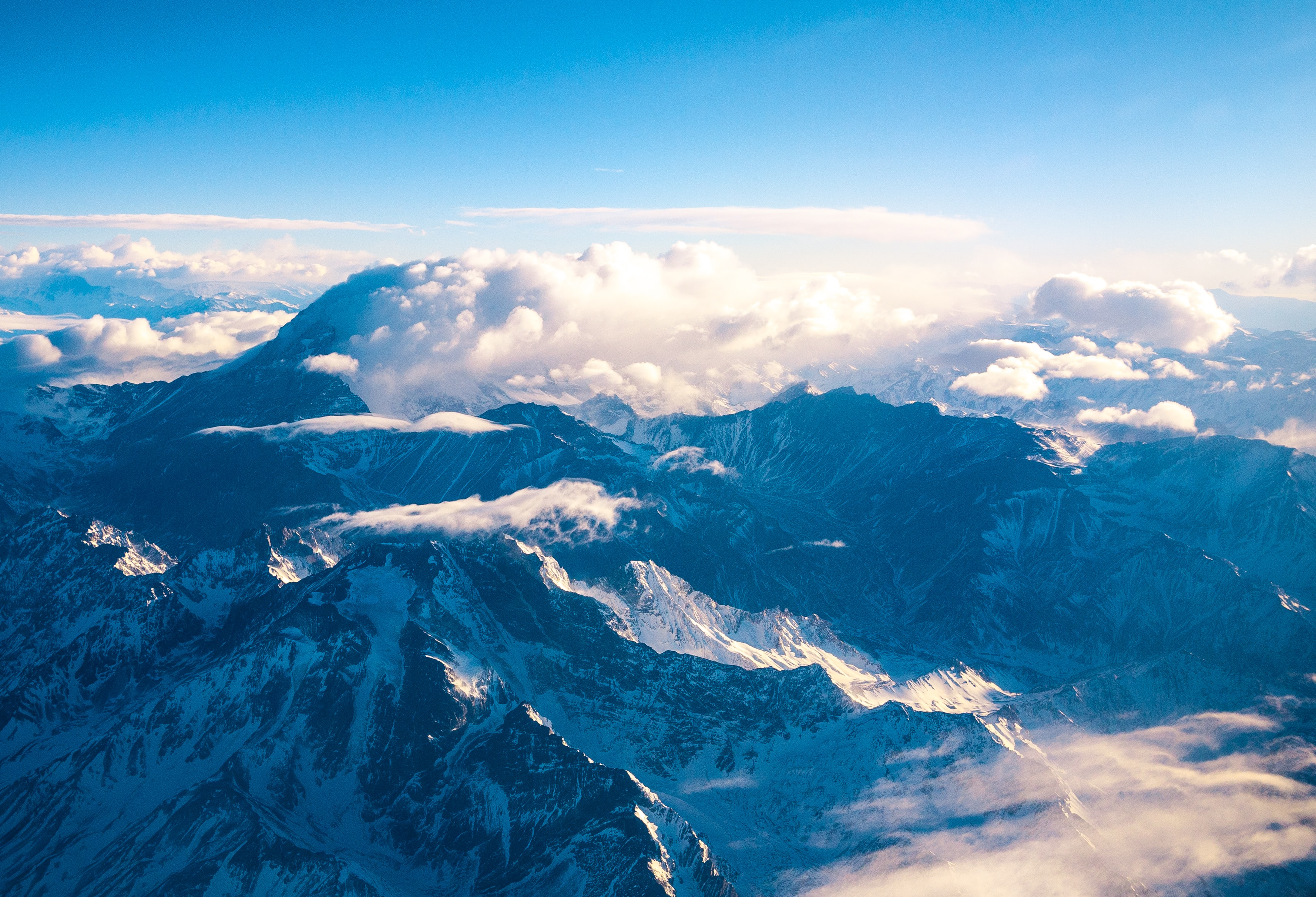 An aerial shot of a tall mountain range under white clouds