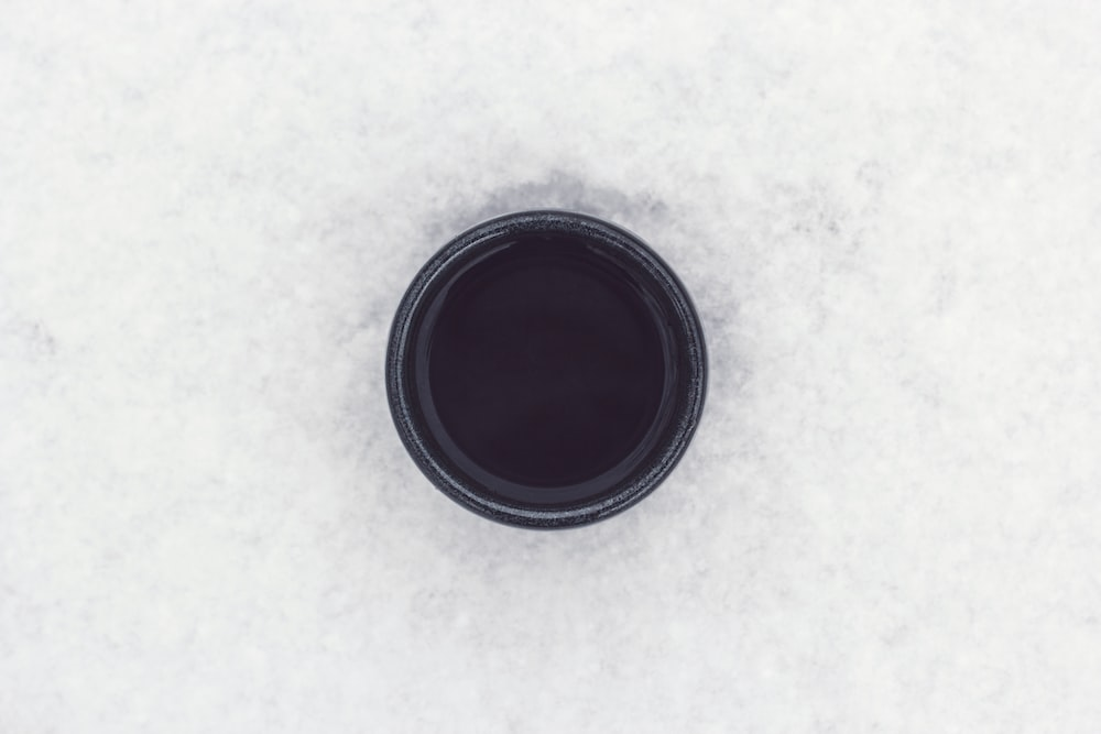 round black container on top of white surface