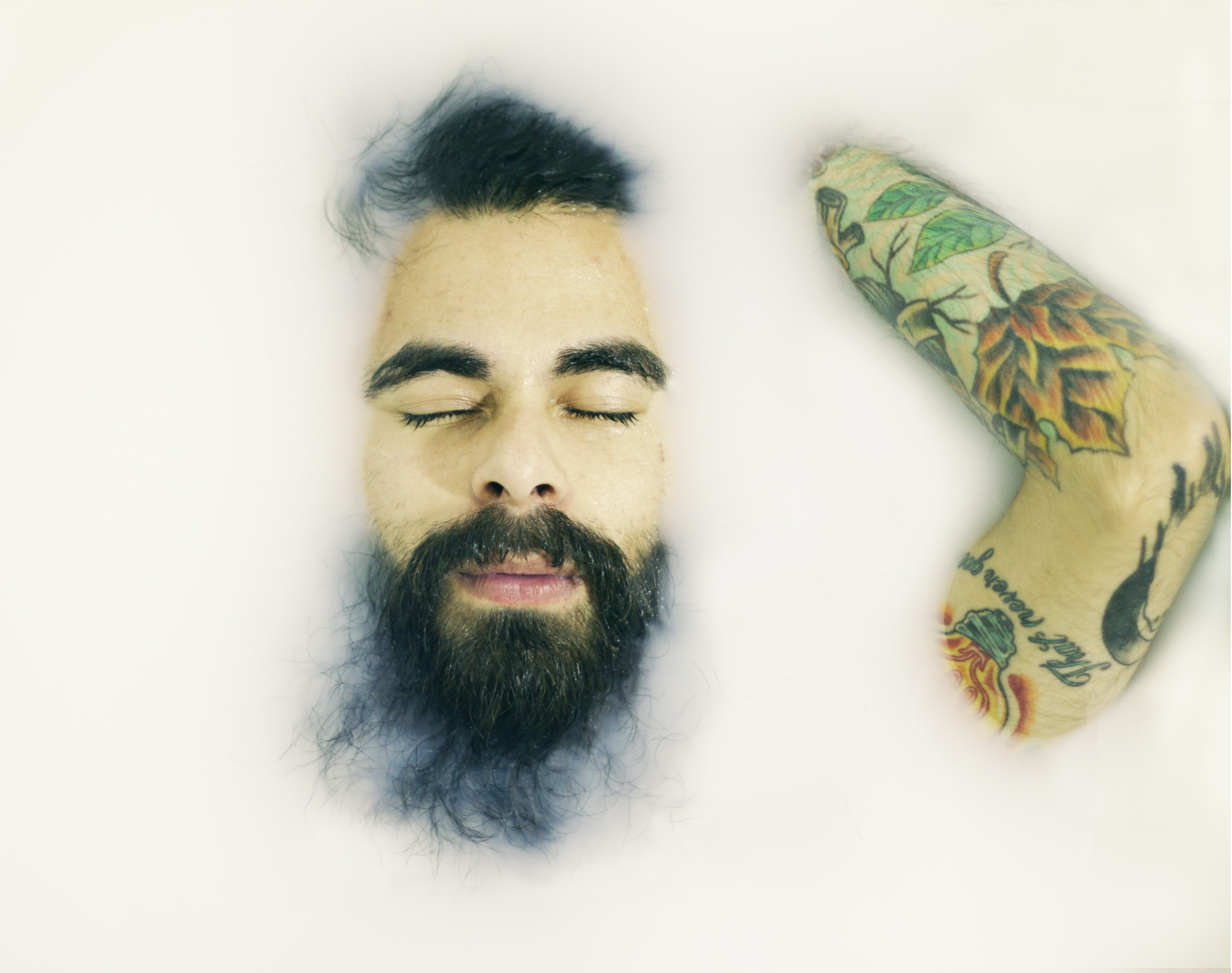 Man with a beard and arm tattoo laying with eyes closed in a milk bath