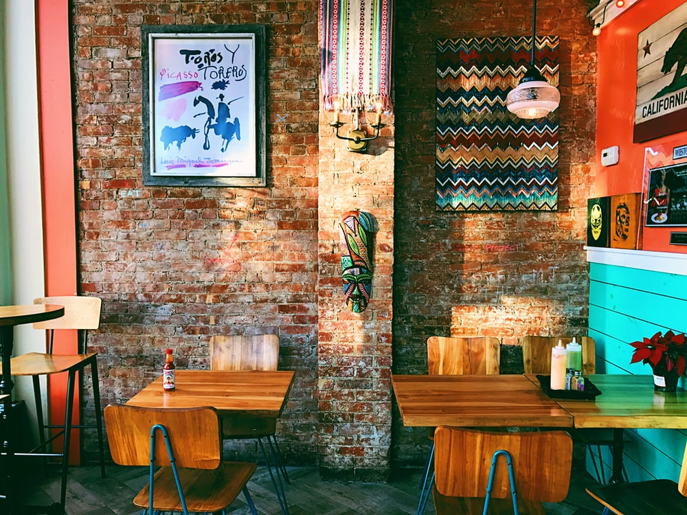 two square brown wooden dining tables near brown brick wall