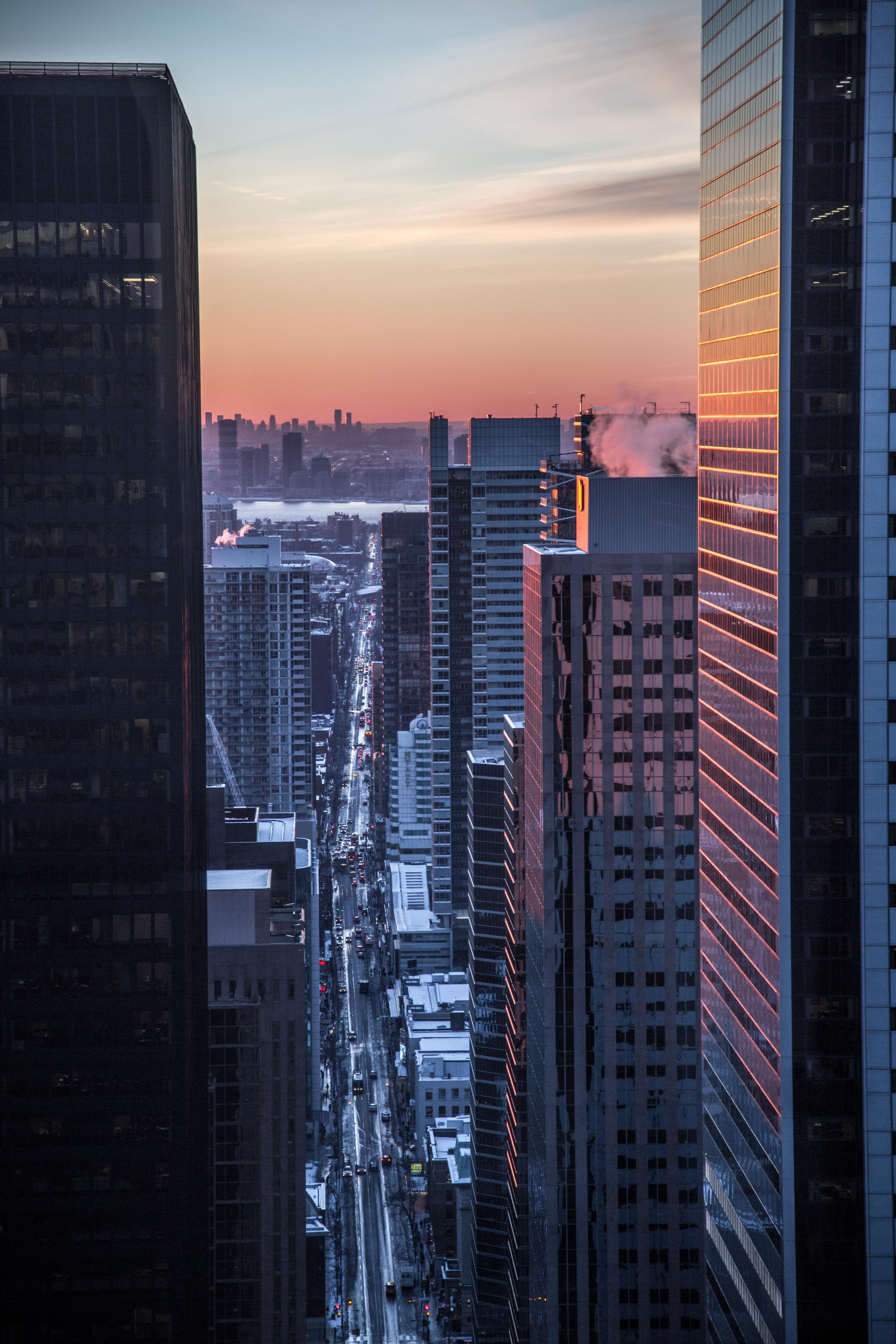 A glimpse of the sunset through with the traffic flowing beneath through the skyscrapers of a city