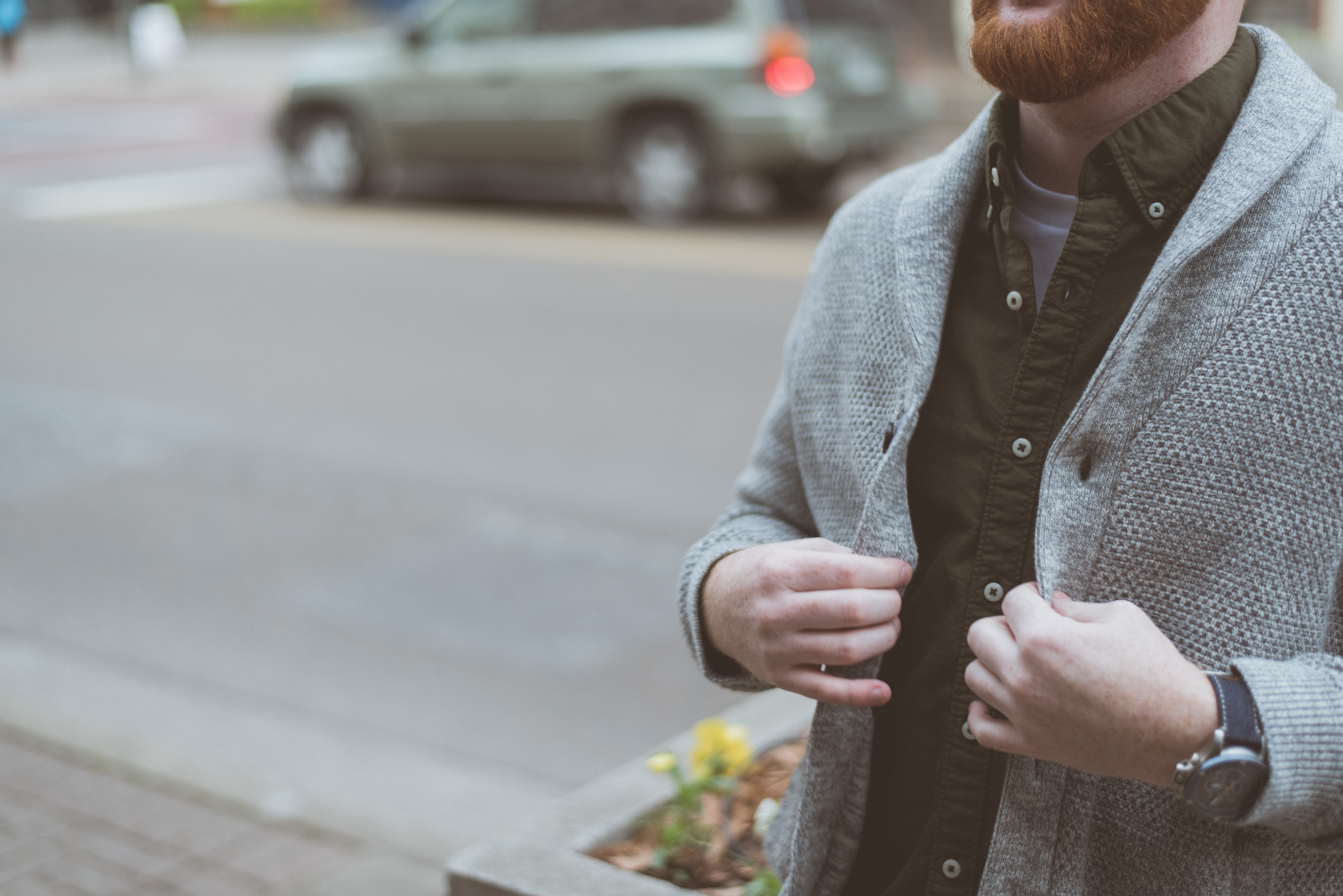 Trendy man with a beard buttoning up his cardigan sweater