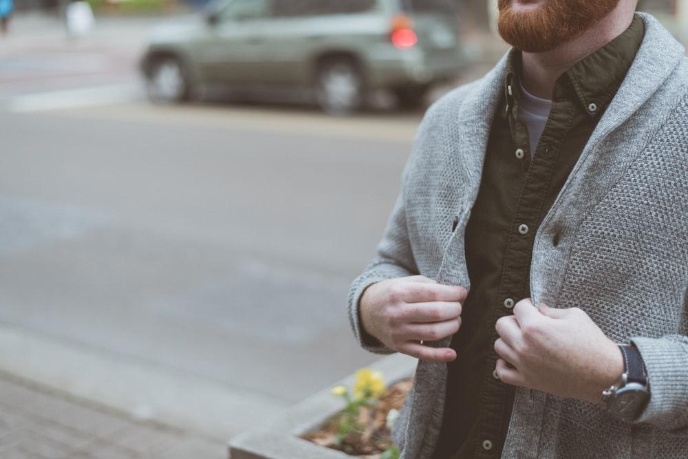 man holding his gray cardigan