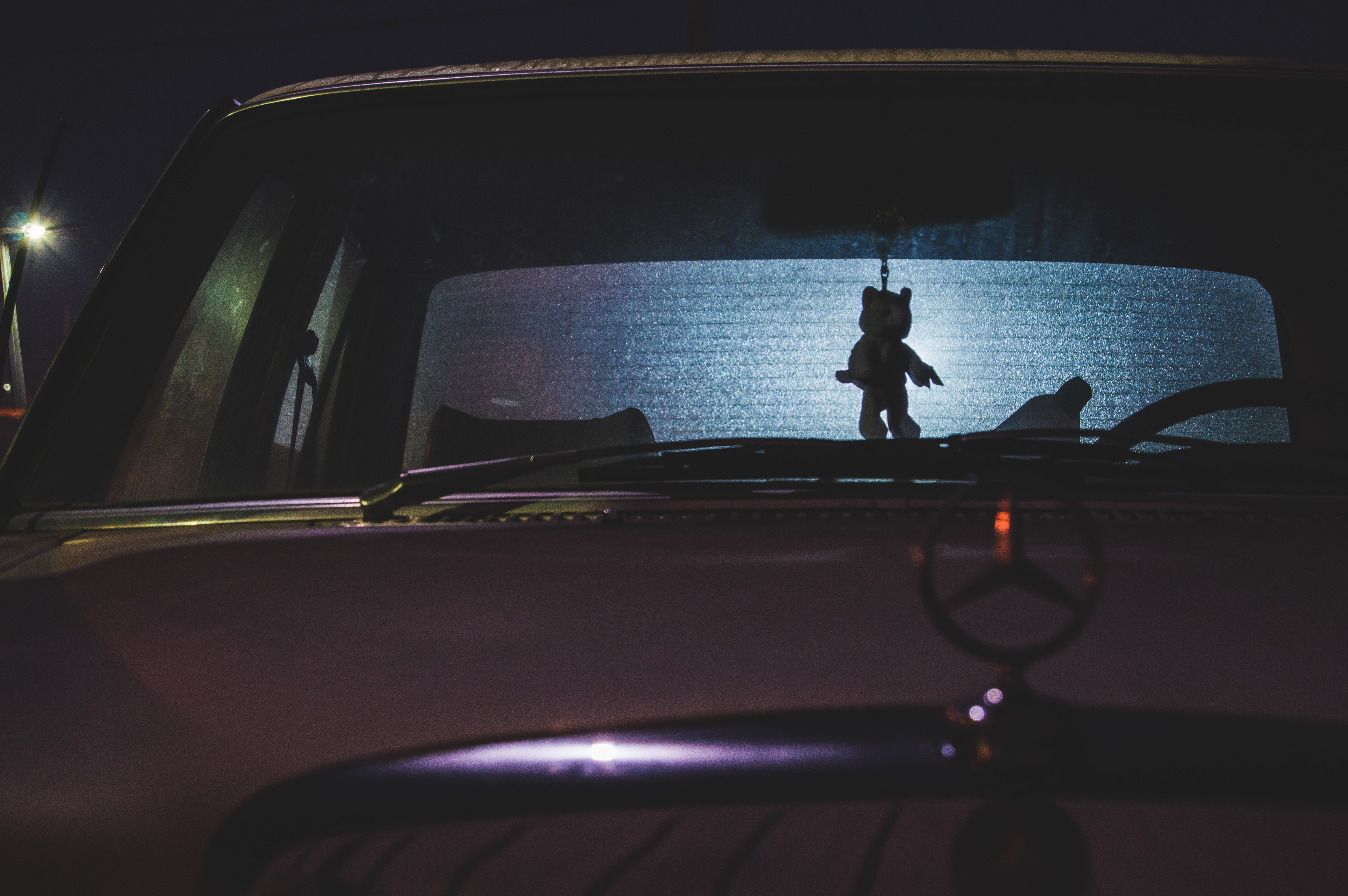 A vintage Mercedes car with a small figurine hanging from the rear-view mirror seen through the windshield.