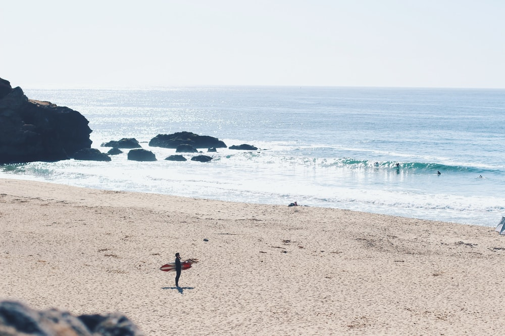 man holding red surfboard on beach