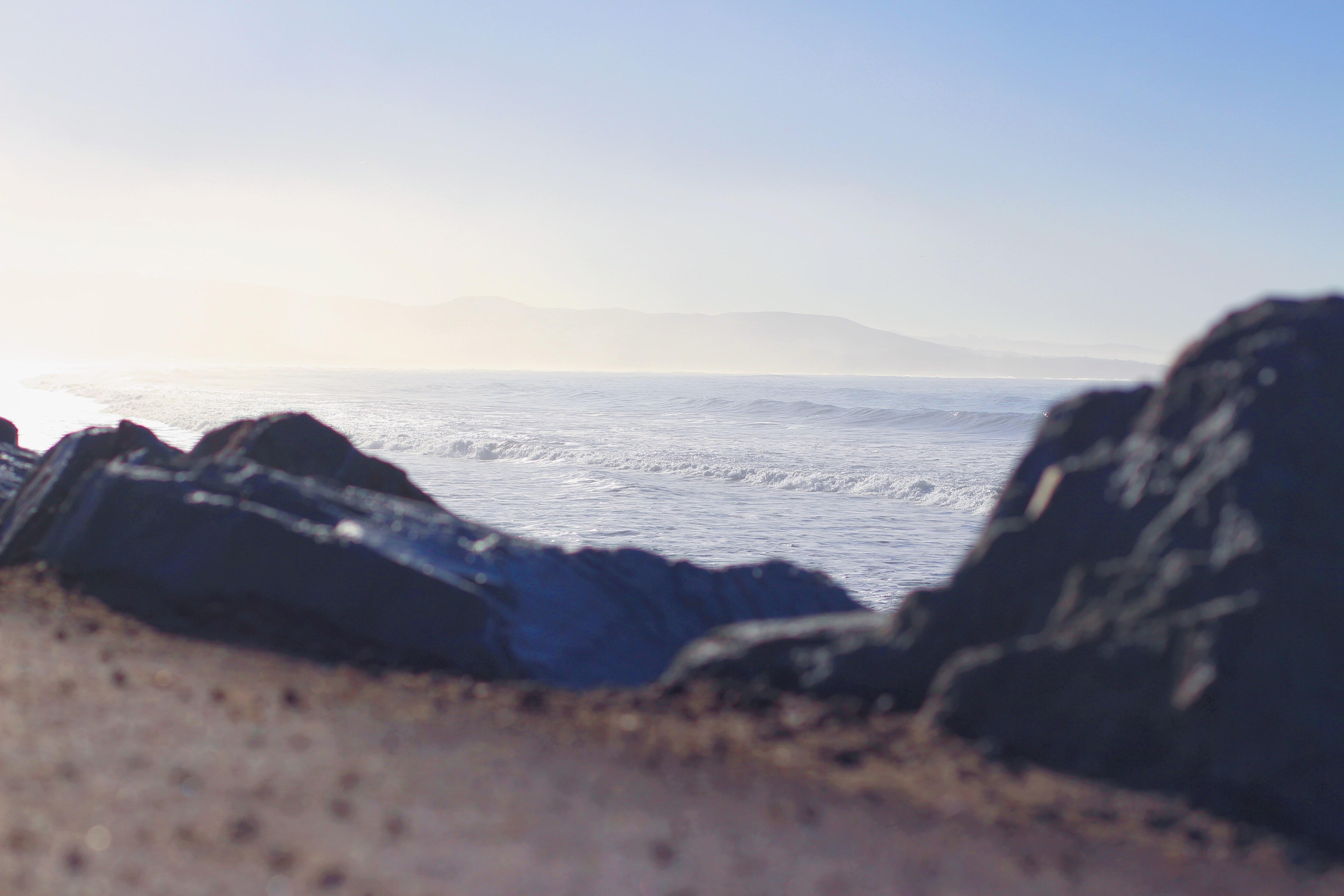 rock mountain near body of water