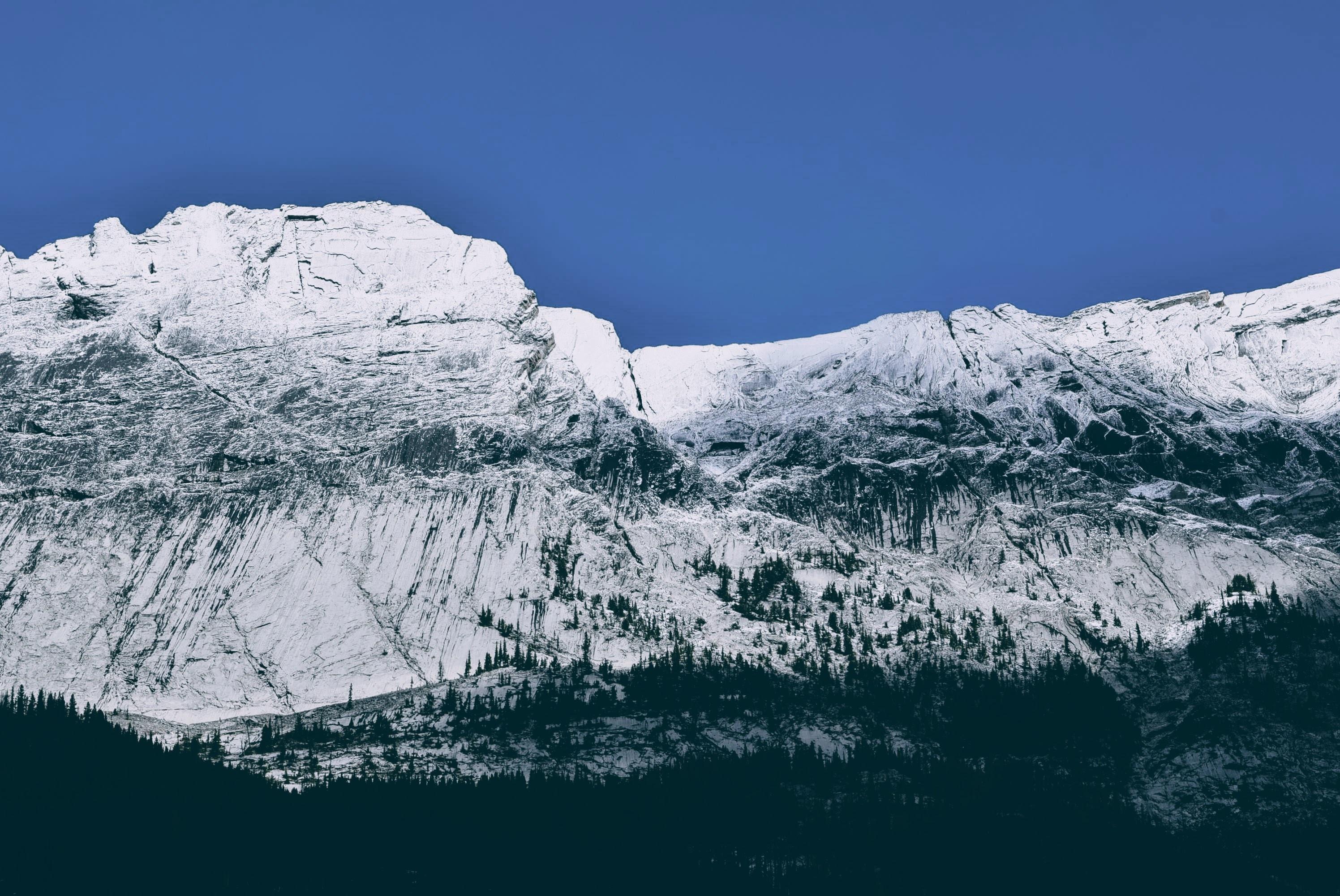 A tall steep mountain face against a blue sky in Jasper National Park